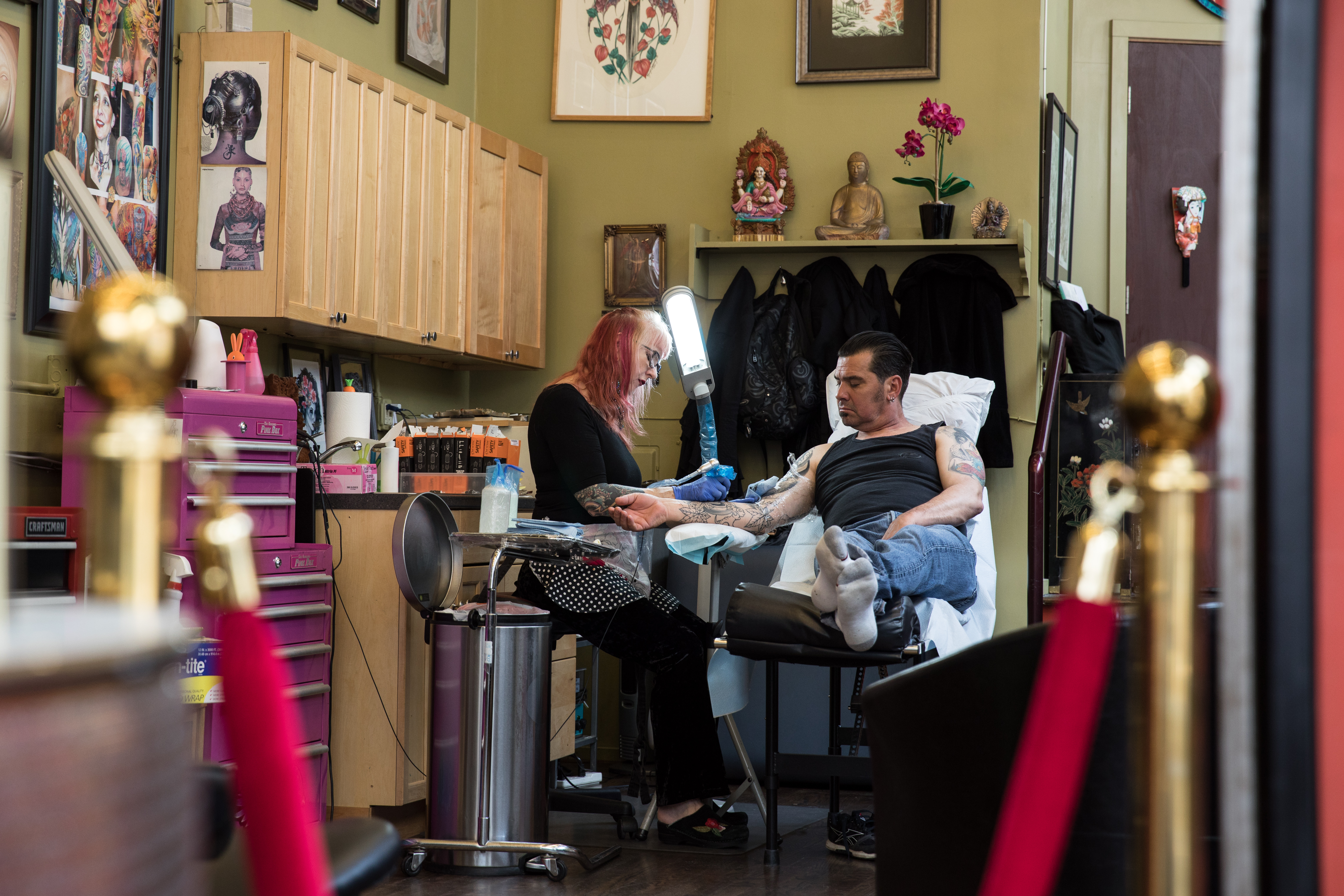 Madame Lazonga's Tattoo studio is decorated in a variety of art ranging from sketches from Vyvyn's earlier years of tattooing to framed articles written about her work. (Image: Riley Bunch / Seattle Refined)
