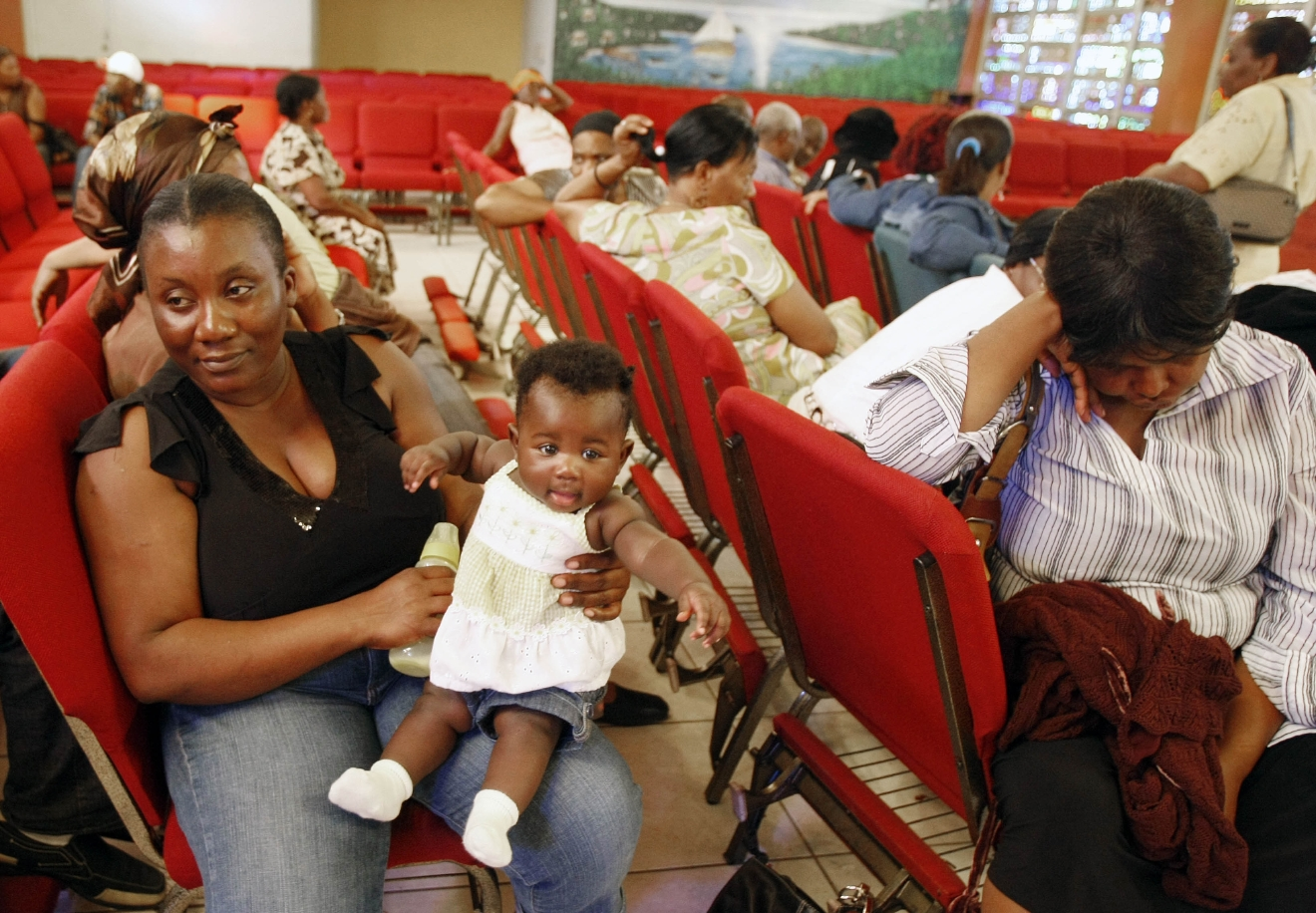 FILE - In this Thursday, Jan. 21, 2010, file photo, Haitian national Carole Manigat, left, holds her daughter Hadassa Carole Albert as she waits for her turn to fill out temporary protective status papers at Notre Dame d'Haiti Catholic Church in the Little Haiti neighborhood in Miami. The U.S. Department of Homeland Security said Thursday, Sept. 22, 2016, that it was widening efforts to deport Haitians, a response to thousands of immigrants from the Caribbean nation who have overwhelmed California border crossings with Mexico in recent months. The move lifts special protections that shielded Haitians from deportation after their nation's 2010 earthquake. (AP Photo/Alan Diaz, File)