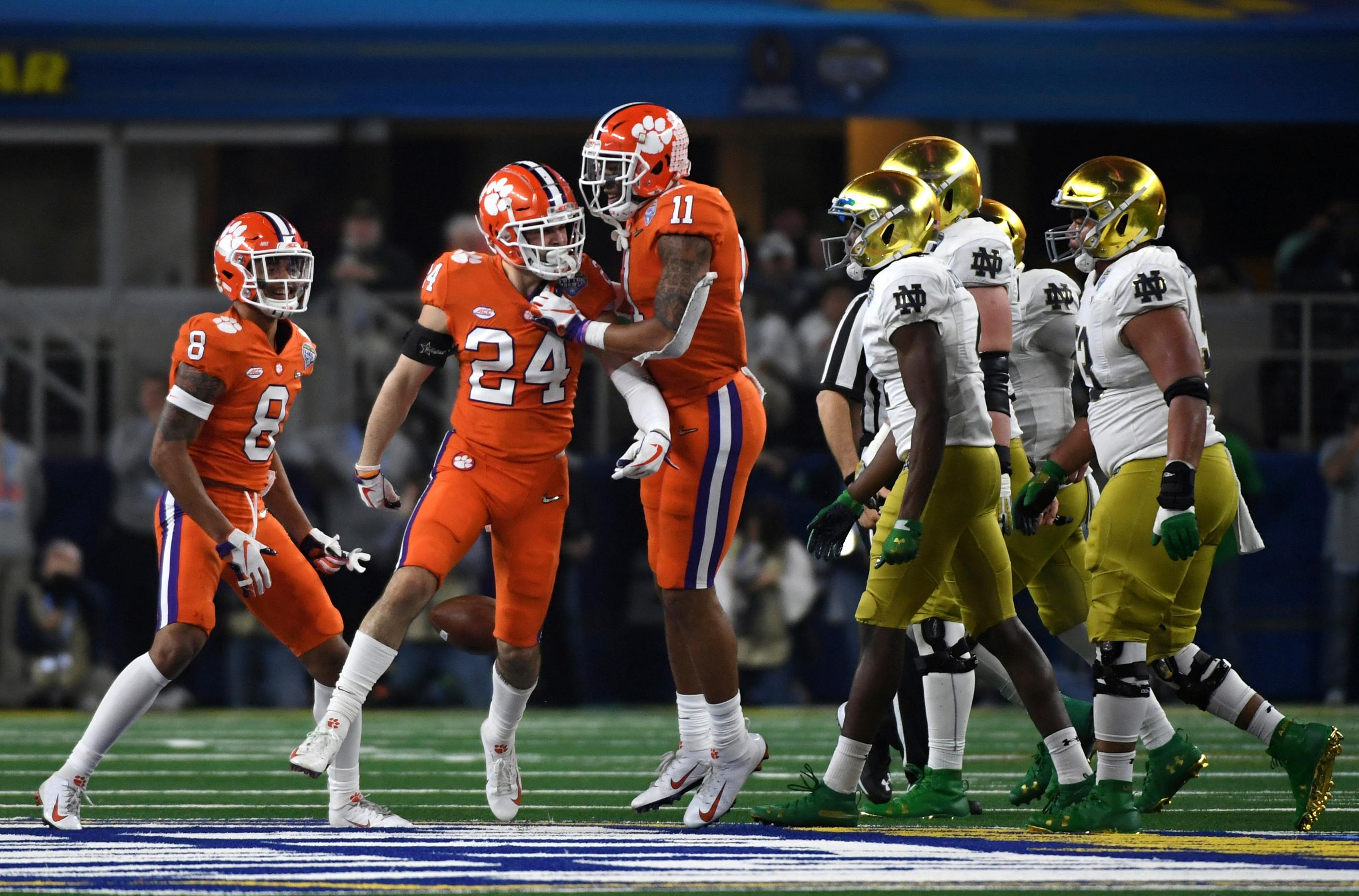 Clemson cornerback A.J. Terrell (8), safety Nolan Turner (24) and safety Isaiah Simmons (11) celebrate a interception thrown by Notre Dame quarterback Ian Book (12) in the second half of the NCAA Cotton Bowl semi-final playoff football game, Saturday, Dec. 29, 2018, in Arlington, Texas. (AP Photo/Jeffrey McWhorter)