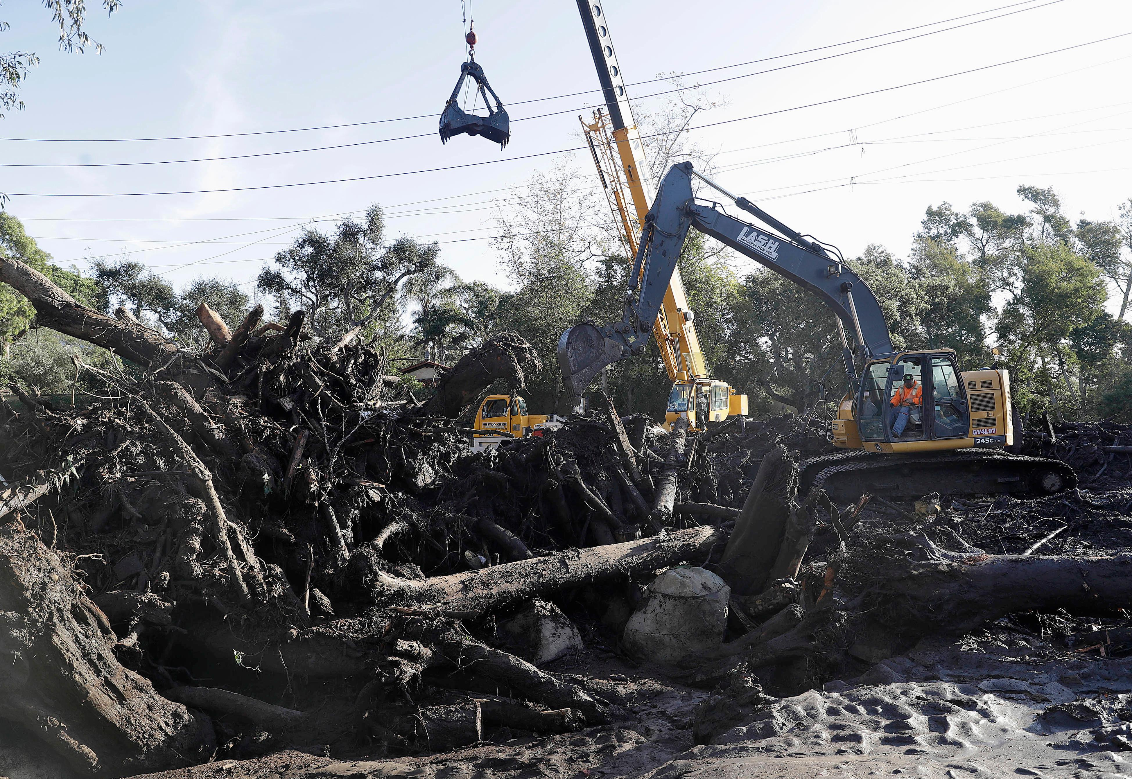 An excavator removes debris from an area damaged by storms in Montecito, Calif., Wednesday, Jan. 10, 2018. Dozens of homes were swept away or heavily damaged and several people were killed Tuesday as downpours sent mud and boulders roaring down hills stripped of vegetation by a gigantic wildfire that raged in Southern California last month. (AP Photo/Marcio Jose Sanchez)