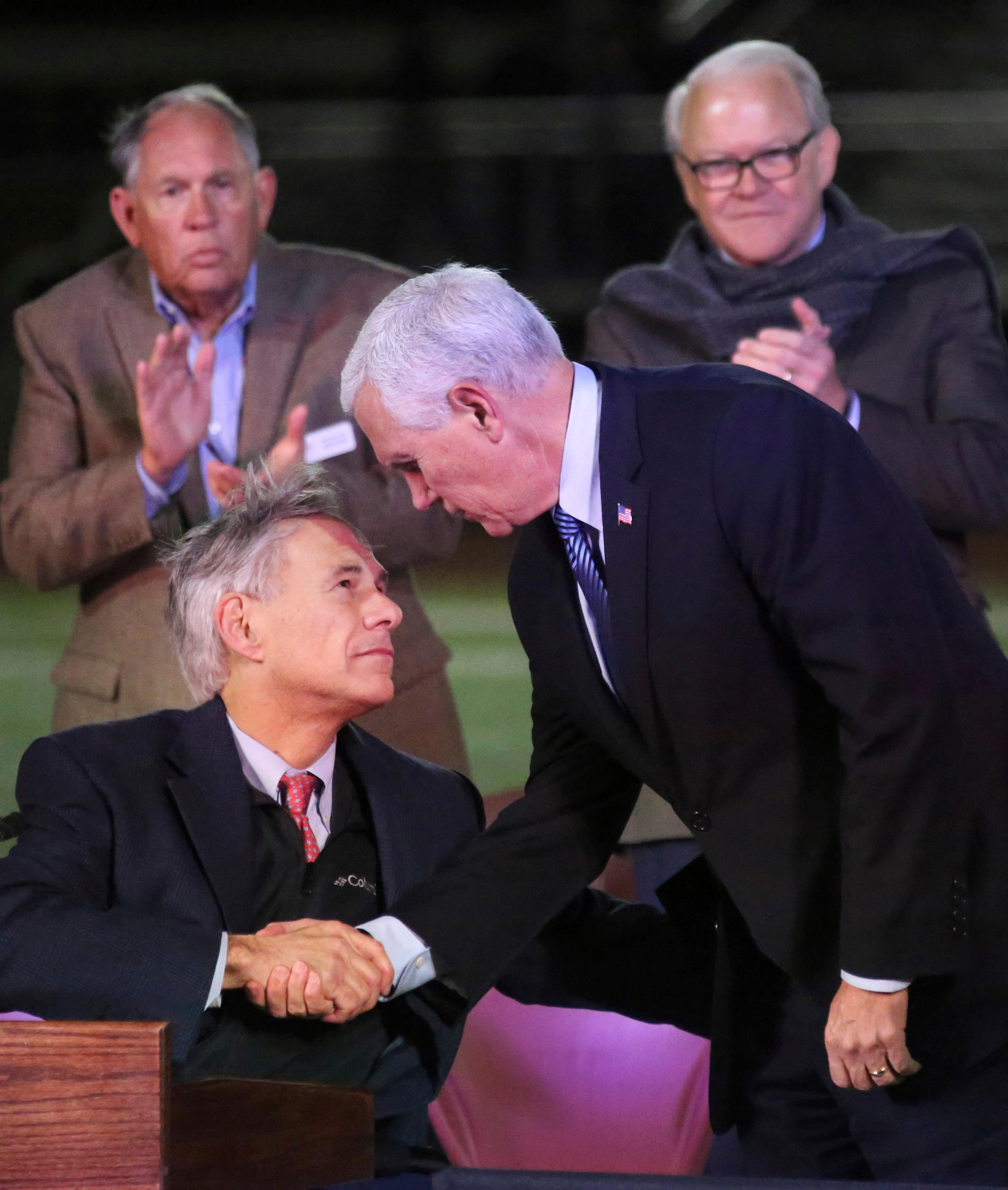 U.S. Vice President Mike Pence, right, shakes hands with Texas Governor Greg Abbott at a prayer vigil for the victims of the shooting at Sutherland Springs First Baptist Church, held at the Floresville High School Football Stadium, Wednesday, Nov. 8, 2017, in Floresville, Texas. (Louis DeLuca/The Dallas Morning News via AP)