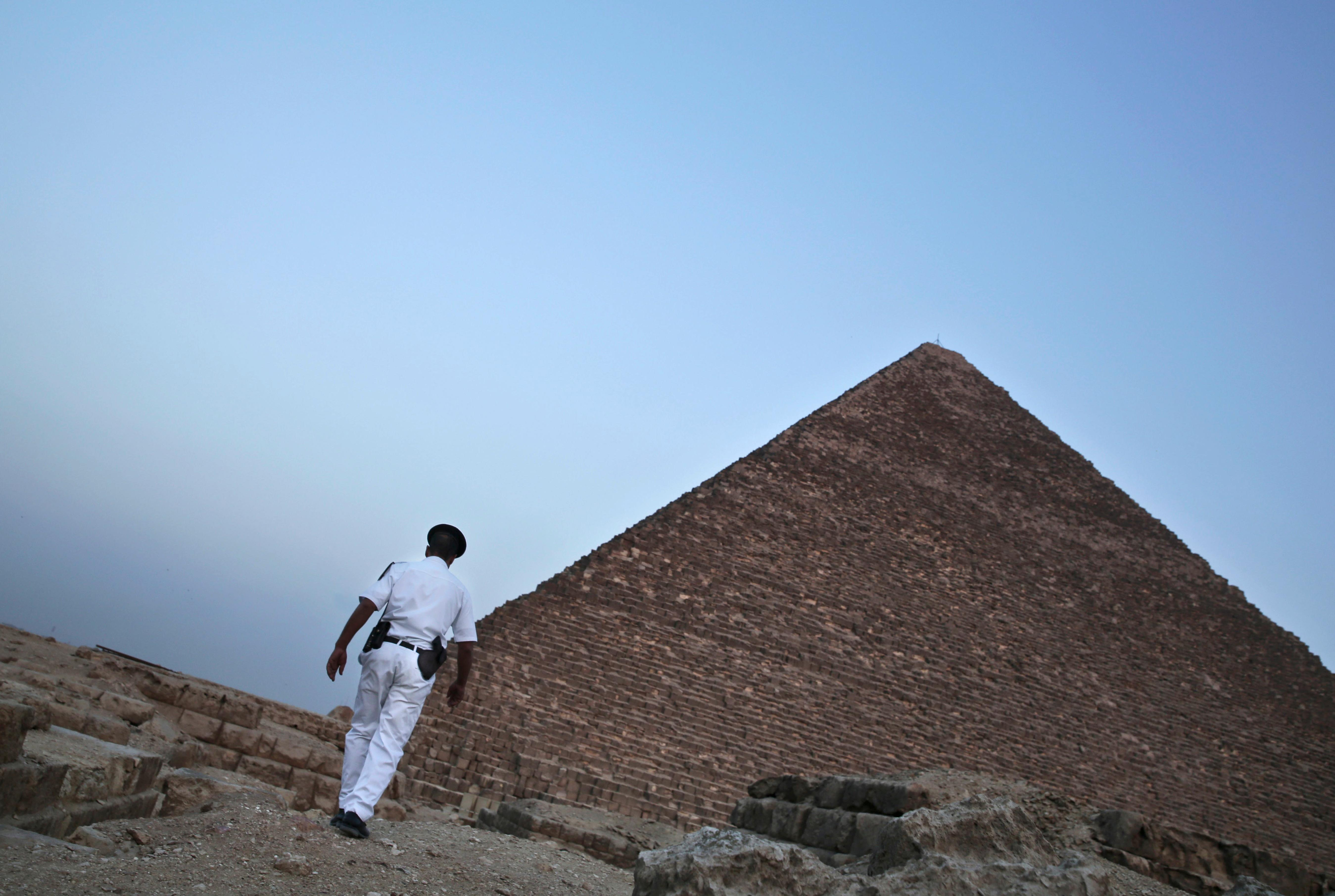 FILE - In this file photo dated Monday, Nov. 9, 2015, an Egyptian policeman walks near a pyramid in Giza, Egypt.  Egypt's Antiquities Ministry on Saturday Feb. 3, 2018, announced the discovery of a 4,400-year-old tomb near the pyramids outside Cairo. (AP Photo/Nariman El-Mofty, FILE)