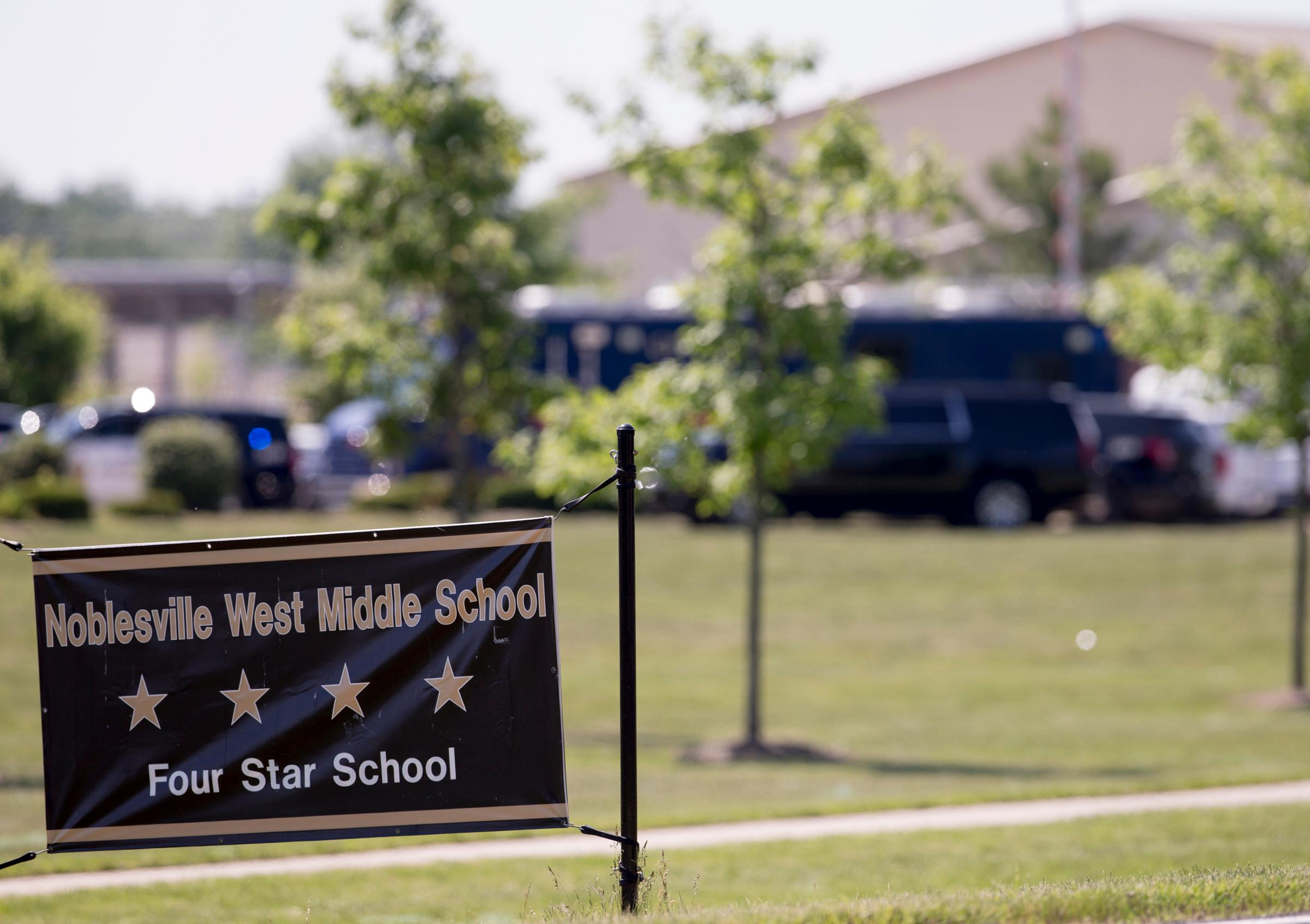 Law enforcement vehicles are seen behind a school sign after a shooting at Noblesville West Middle School in Noblesville, Ind., on Friday, May 25, 2018. A male student opened fire at the suburban Indianapolis school wounding another student and a teacher before being taken into custody, authorities said. (Robert Scheer/The Indianapolis Star via AP)