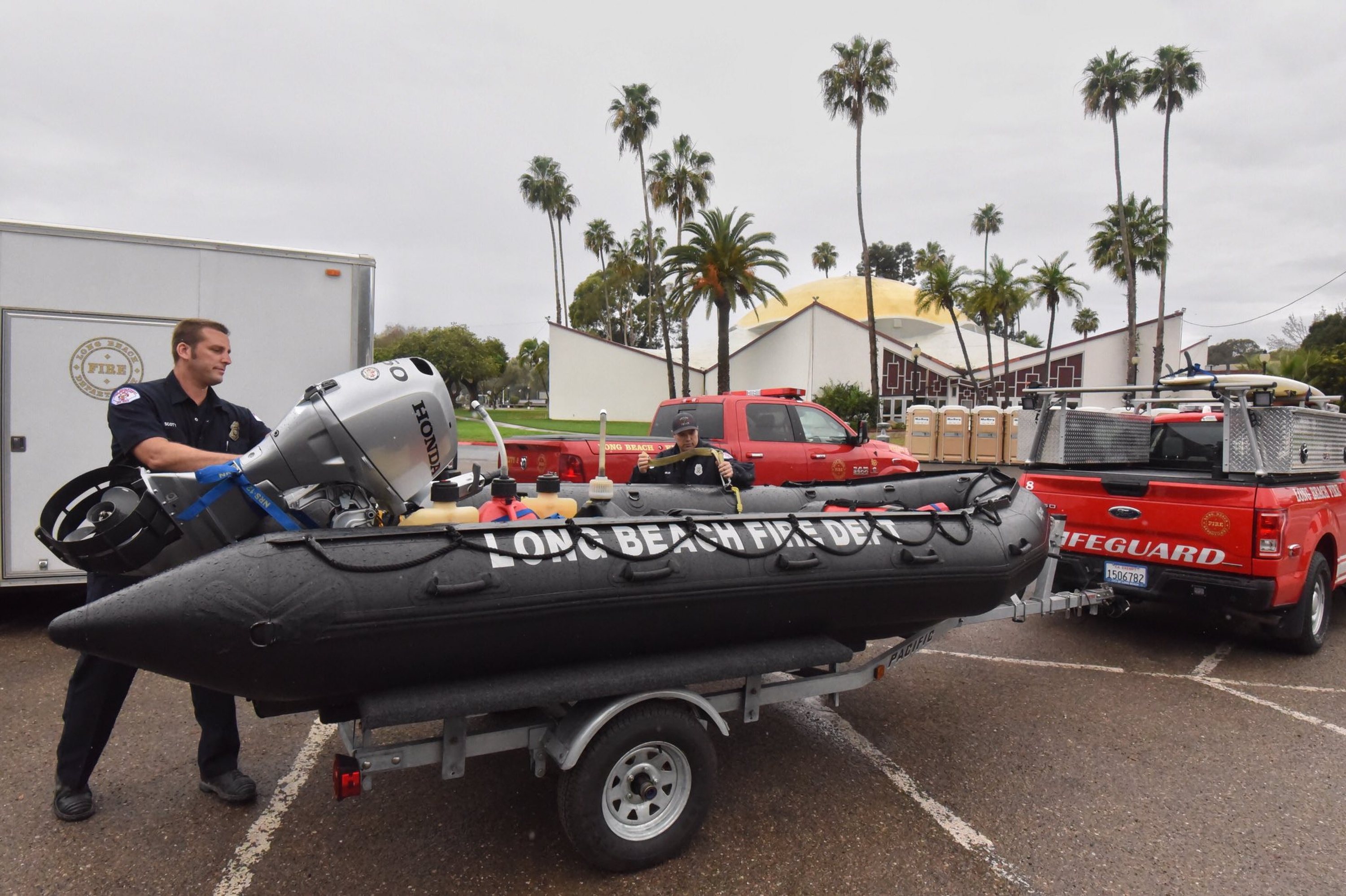 In this photo released by Santa Barbara County Fire Department, members of the Long Beach Fire Department Swift Water Rescue Team check equipment while staged at Earl Warren Showgrounds in Santa Barbara, Calif., Monday, Jan. 8, 2018. The team will respond if needed for any area flooding in the Montecito or Carpinteria areas. (Mike Eliason/Santa Barbara County Fire Department via AP)