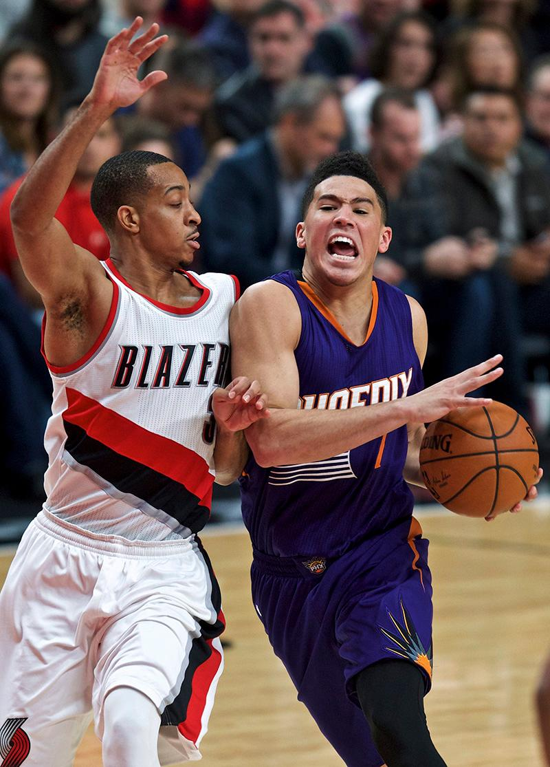 Phoenix Suns guard Devin Booker, right, drives to the basket past Portland Trail Blazers guard C.J. McCollum during the second half of an NBA basketball game in Portland, Ore., Tuesday, Nov. 8, 2016. (AP Photo/Craig Mitchelldyer)