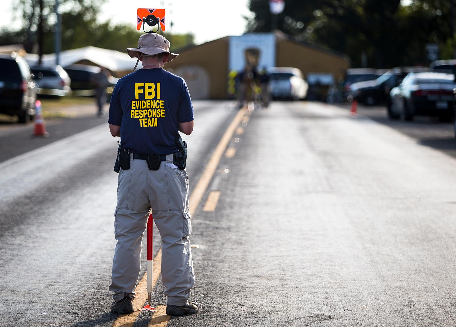 A member of the FBI's Evidence Response Team works on the crime scene of the mass shooting at the First Baptist Church in Sutherland Springs, Texas on Monday, Nov. 6, 2017. (Nick Wagner/Austin American-Statesman via AP)