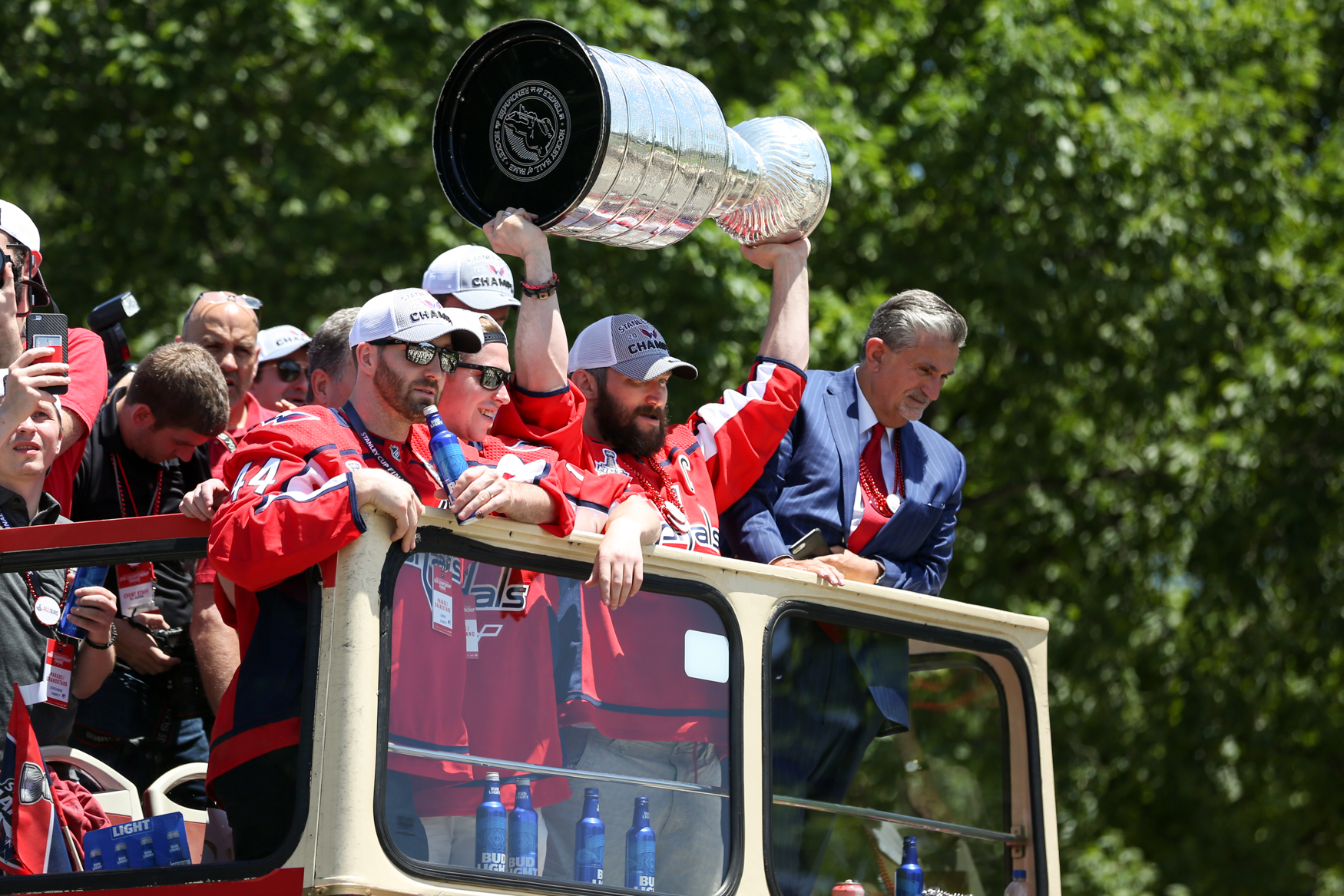 Alex Ovechkin hoists the cup over his head, alongside teammates Brooks Orpik and Nicklas Backstrom and Caps owner Ted Leonsis. (Amanda Andrade-Rhoades/DC Refined)
