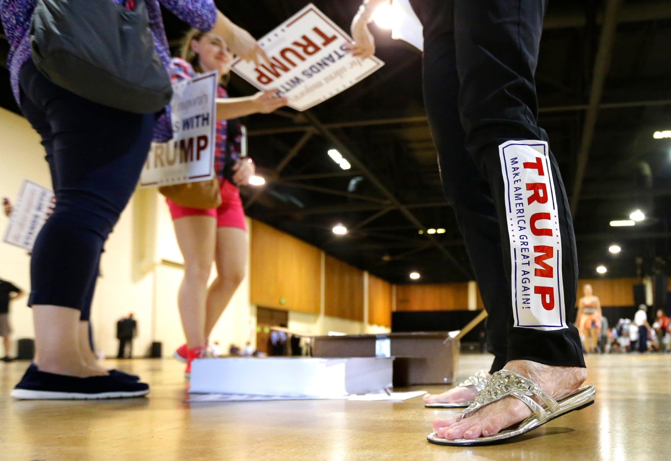 Volunteer Donna Cowan wears a Donald Trump bumper sticker on her leg as she hands out signs before a the start of a rally for the Republican presidential candidate in Eugene, Ore., Friday, May 6, 2016. (AP Photo/Ted S. Warren)