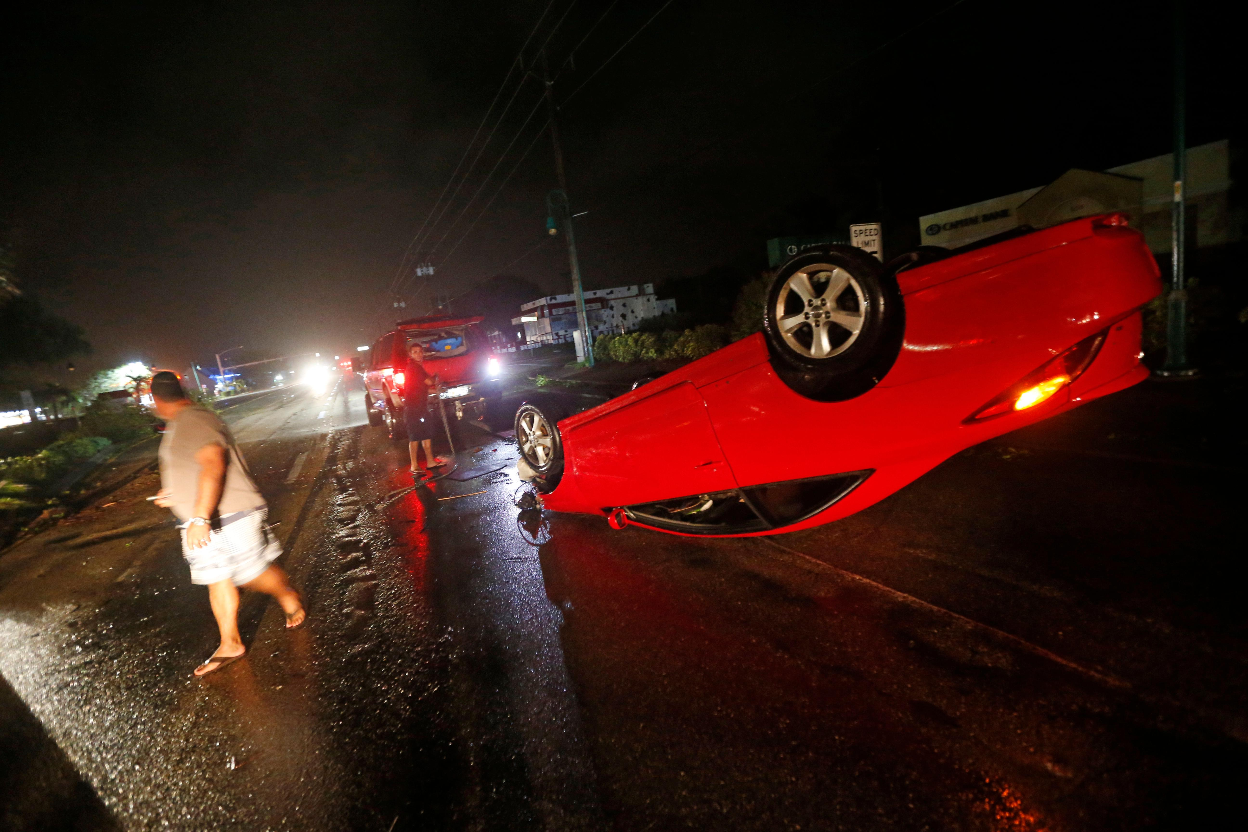People tend to a car that flipped over on Cape Coral Parkway during Hurricane Irma, in Cape Coral, Fla., Sunday, Sept. 10, 2017. (AP Photo/Gerald Herbert)