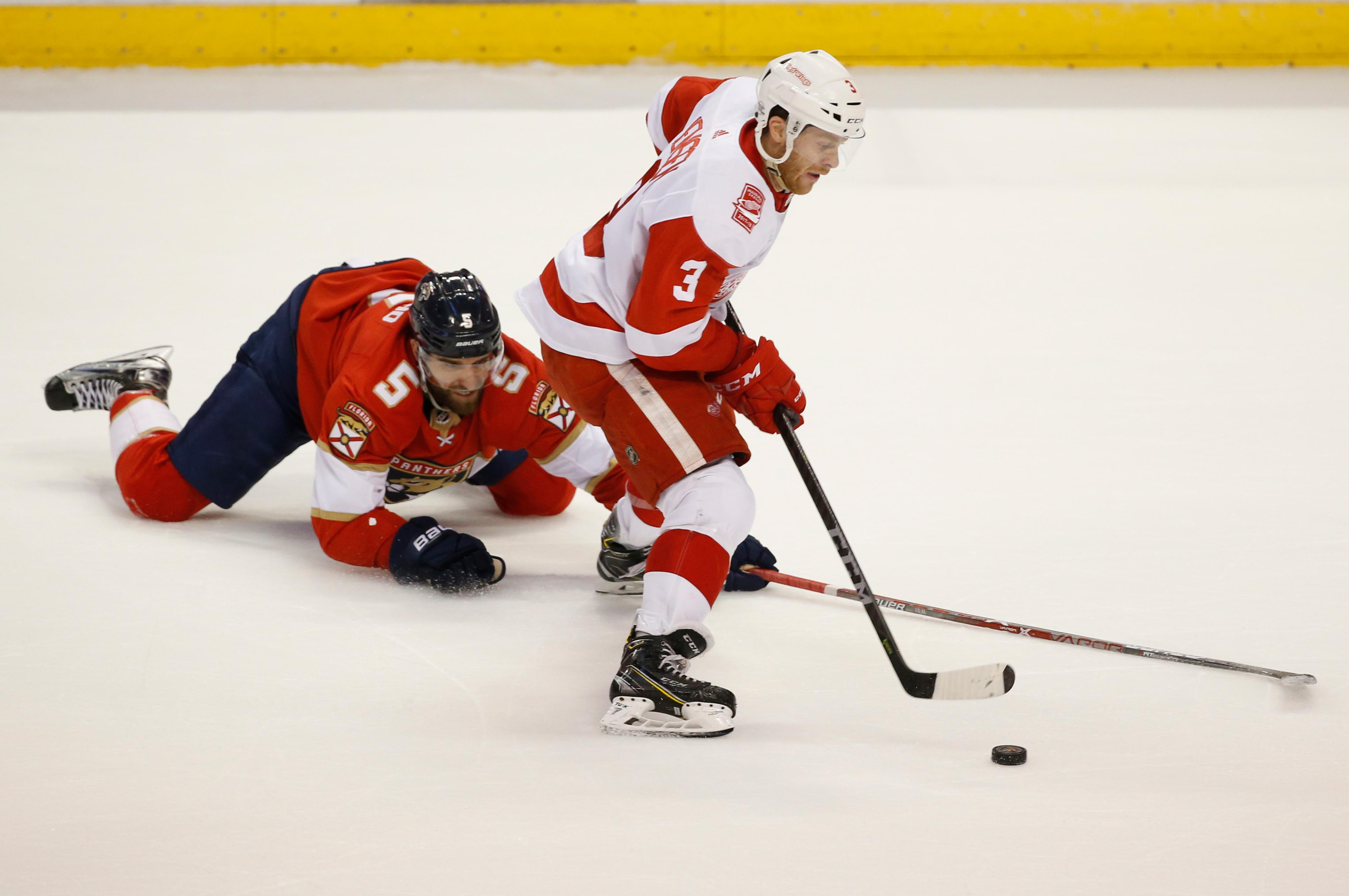 Detroit Red Wings defenseman Nick Jensen (3) battles for the puck with Florida Panthers defenseman Aaron Ekblad (5) during the first period of an NHL hockey game, Saturday, Feb. 3, 2018 in Sunrise, Fla. (AP Photo/Wilfredo Lee)