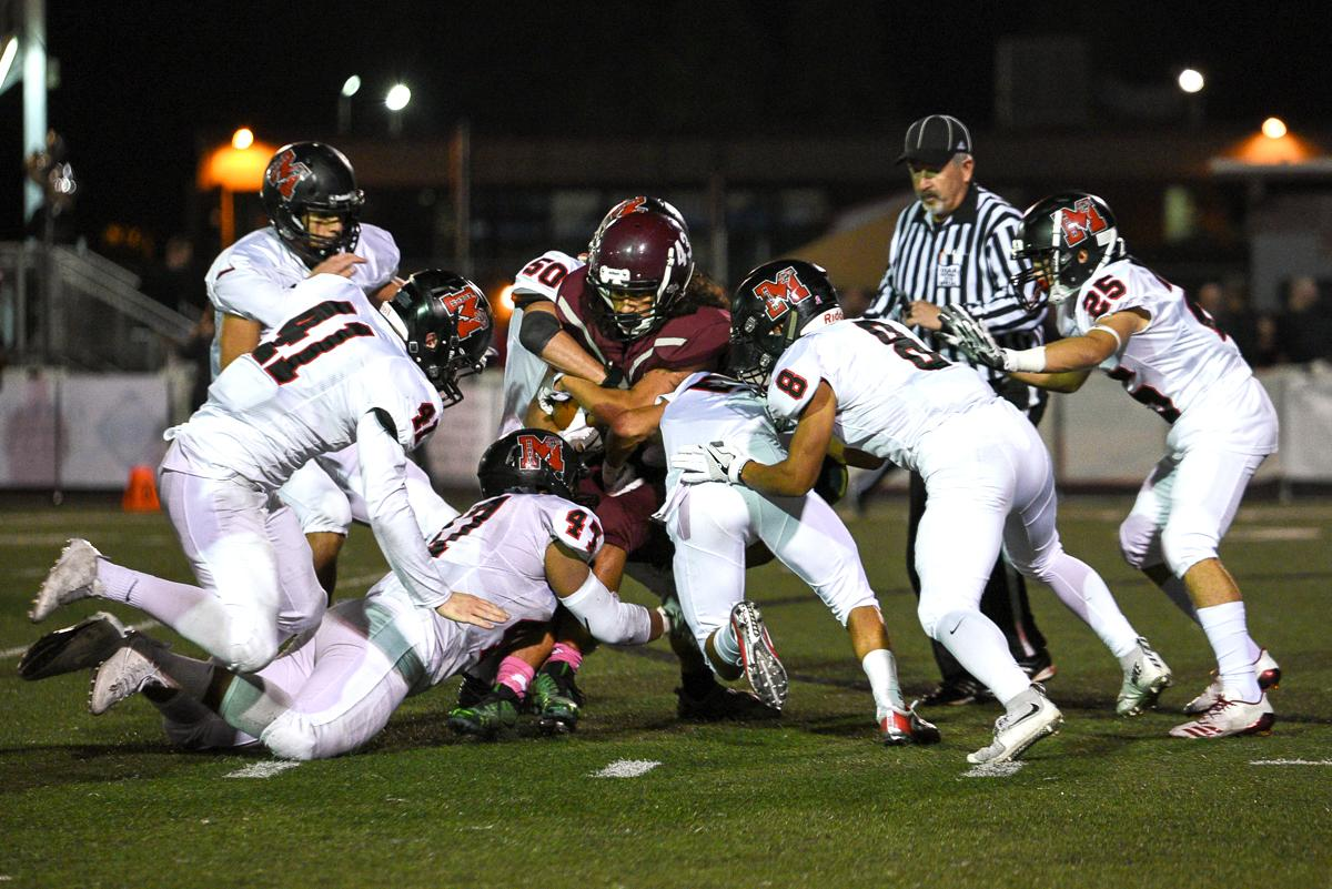 Willamette running back Kalvyn Young (#43) is tackled by a group of North Medford defenders during Willamette's 45-19 loss to North Medford. Photo by Jeff Dean, Oregon News Lab