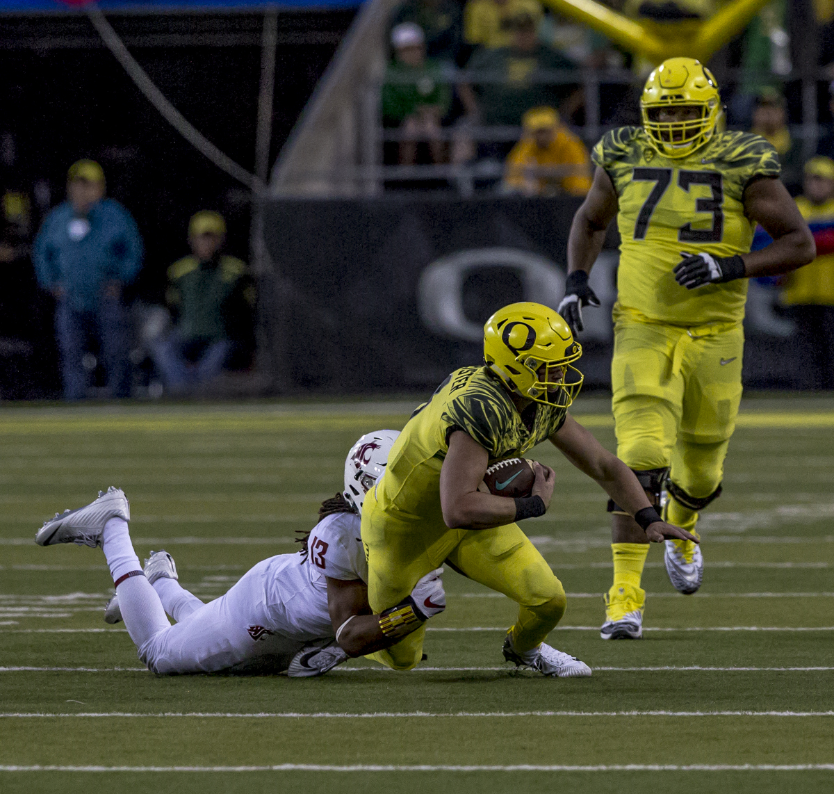 Oregon quarterback Braxton Burmeister (#11) carries the ball on a quarterback keeper. The Oregon Ducks trail the Washington State Cougars 10 to 13 at the end of the first half. Photo by Ben Lonergan, Oregon News Lab