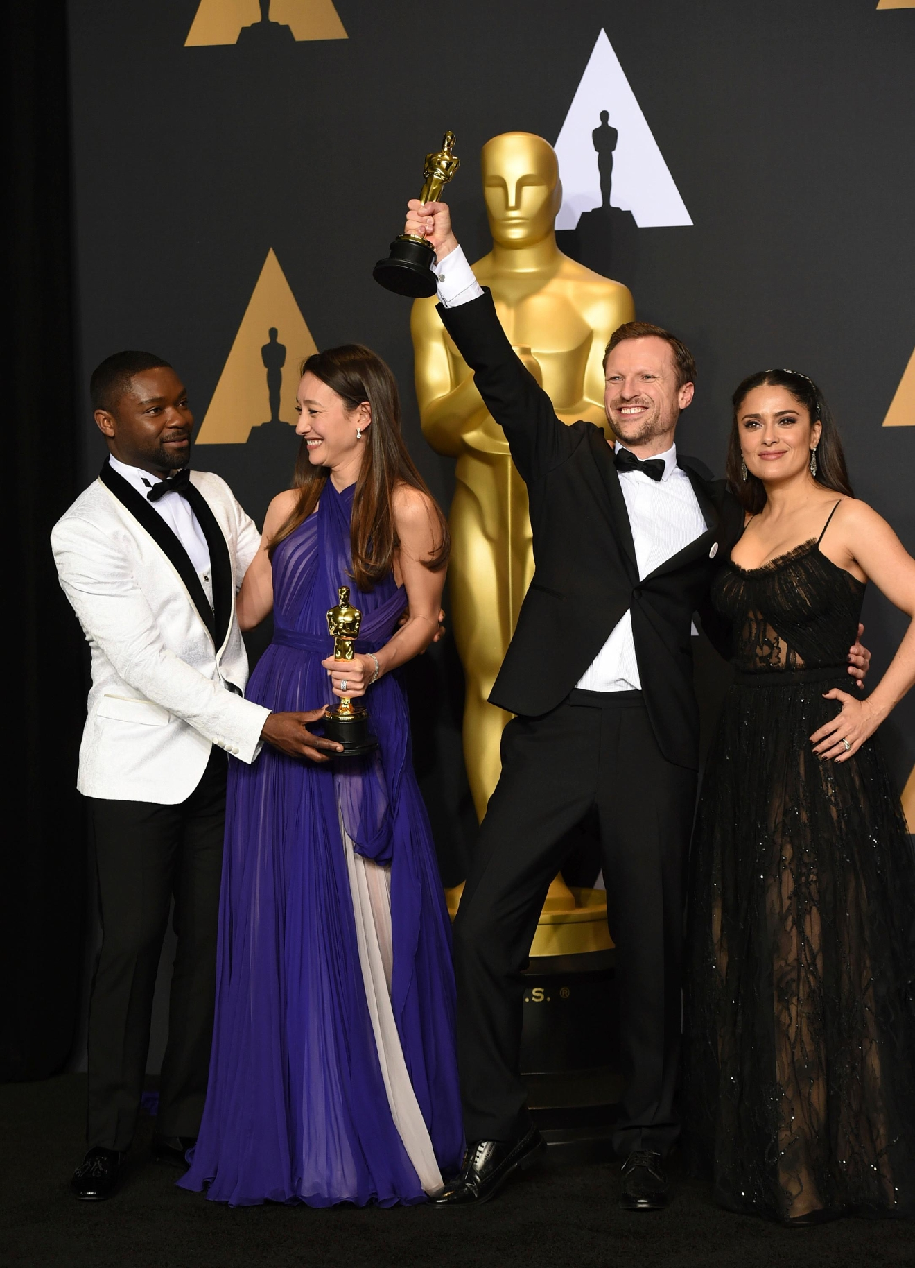 "Joanna Natasegara, second from left, and Orlando von Einsiedel, winners of the award for for best documentary short subject for ""The White Helmets,"" pose in the press room with David Oyelowo, left, and Salma Hayek, right, at the Oscars on Sunday, Feb. 26, 2017, at the Dolby Theatre in Los Angeles. (Photo by Jordan Strauss/Invision/AP)"