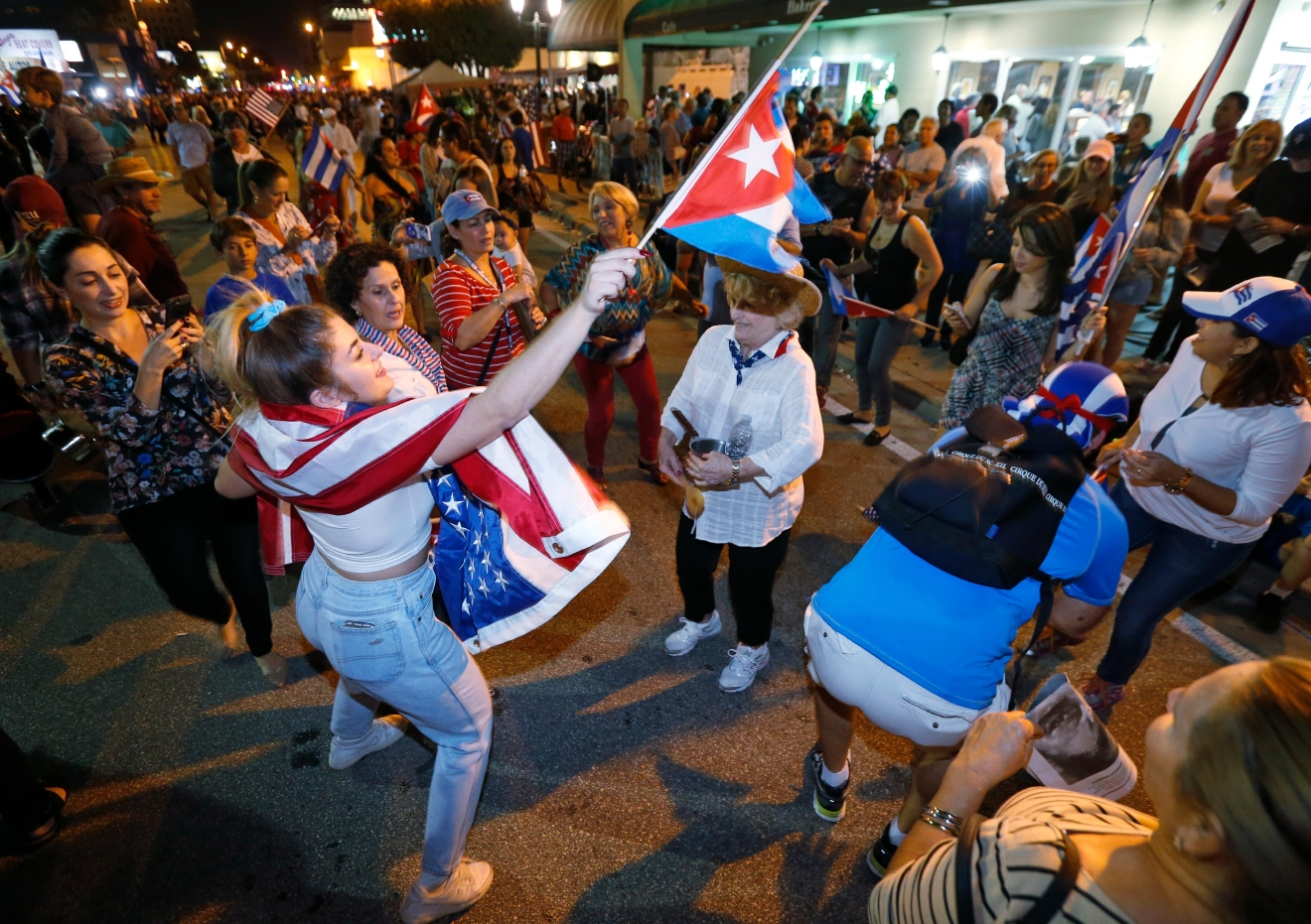 FILE- In this Nov. 26, 2016, file photo, members of the Cuban community dance in the street as they react to the death of Fidel Castro in front of the Versailles Restaurant in the Little Havana neighborhood of Miami. (AP Photo/Wilfredo Lee, File)