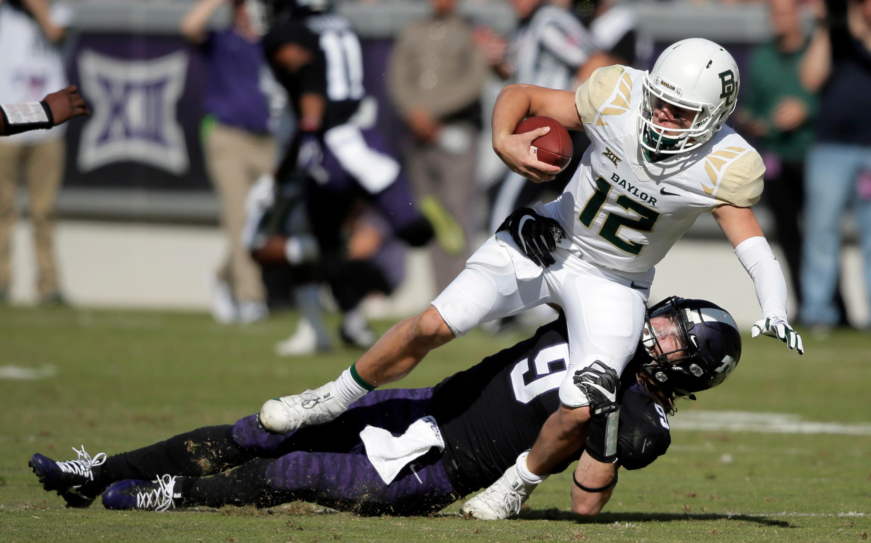 TCU defensive end Mat Boesen (9) tackles Baylor quarterback Charlie Brewer (12) during the first half of an NCAA college football game, Friday, Nov. 24, 2017, in Fort Worth, Texas. (AP Photo/Brandon Wade)