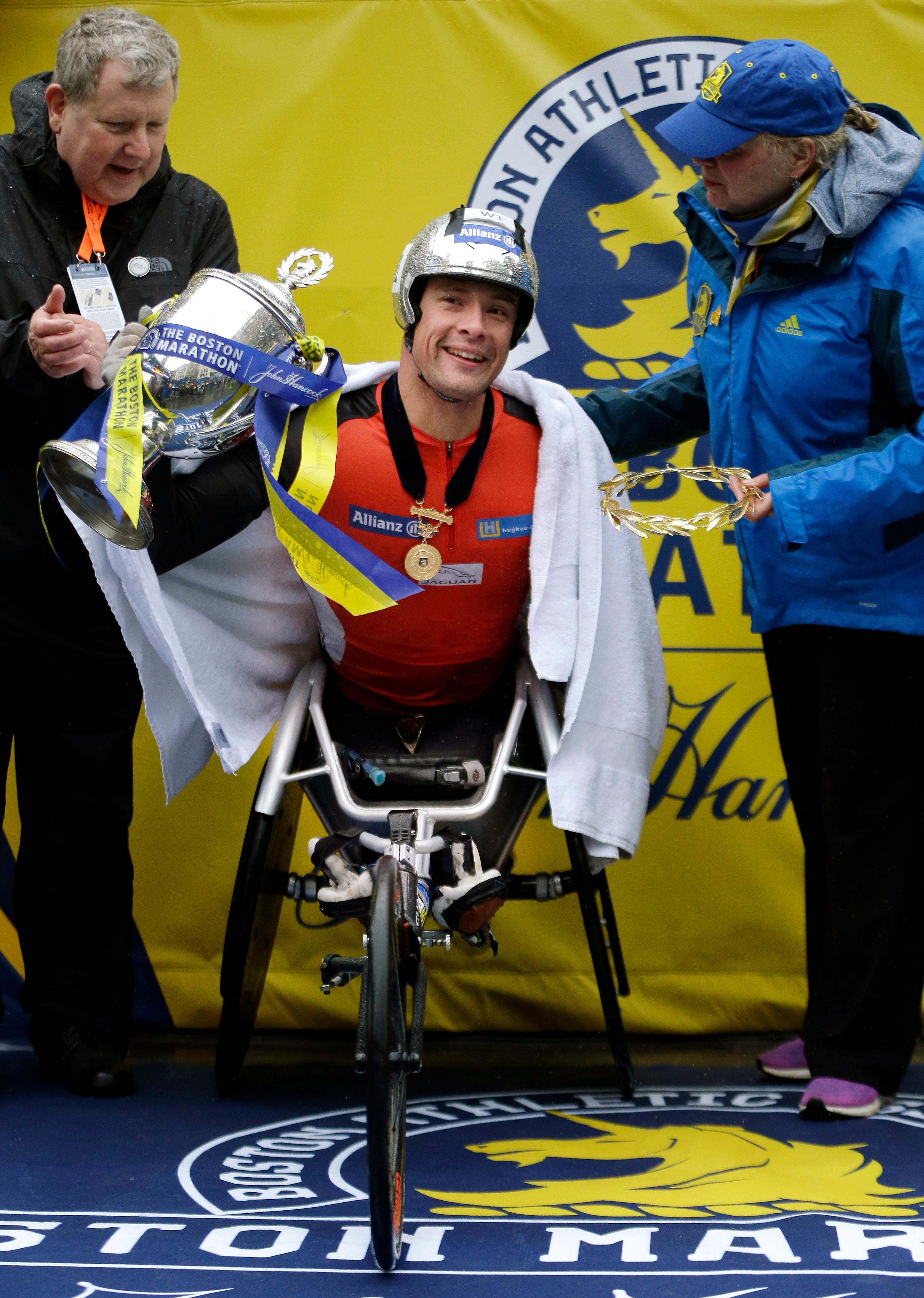 Marcel Hug, of Switzerland, lifts the trophy after winning the men's wheelchair division of the 122nd Boston Marathon on Monday, April 16, 2018, in Boston. (AP Photo/Elise Amendola)