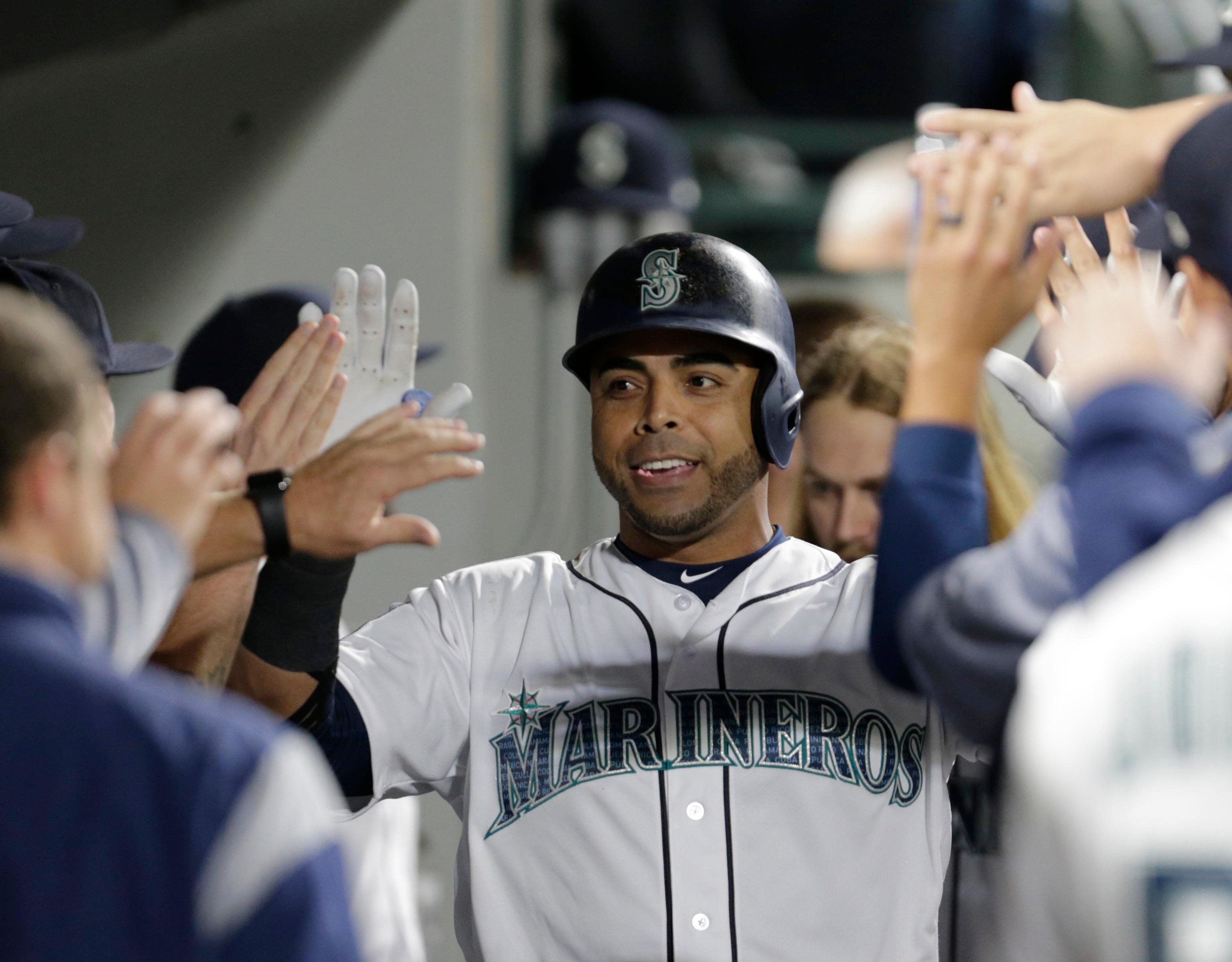 Seattle Mariners' Nelson Cruz is congratulated in the dugout after hitting a three-run home run off Los Angeles Angels' Jesse Chavez during the fourth inning of a baseball game Saturday, Sept. 9, 2017, in Seattle. (AP Photo/John Froschauer)