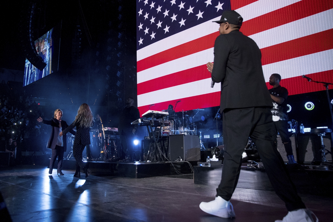 Democratic presidential candidate Hillary Clinton, left, is welcomed to the stage by artists Jay Z, right, and Beyonce, second from left, during a free concert at at the Wolstein Center in Cleveland, Friday, Nov. 4, 2016. (AP Photo/Andrew Harnik)