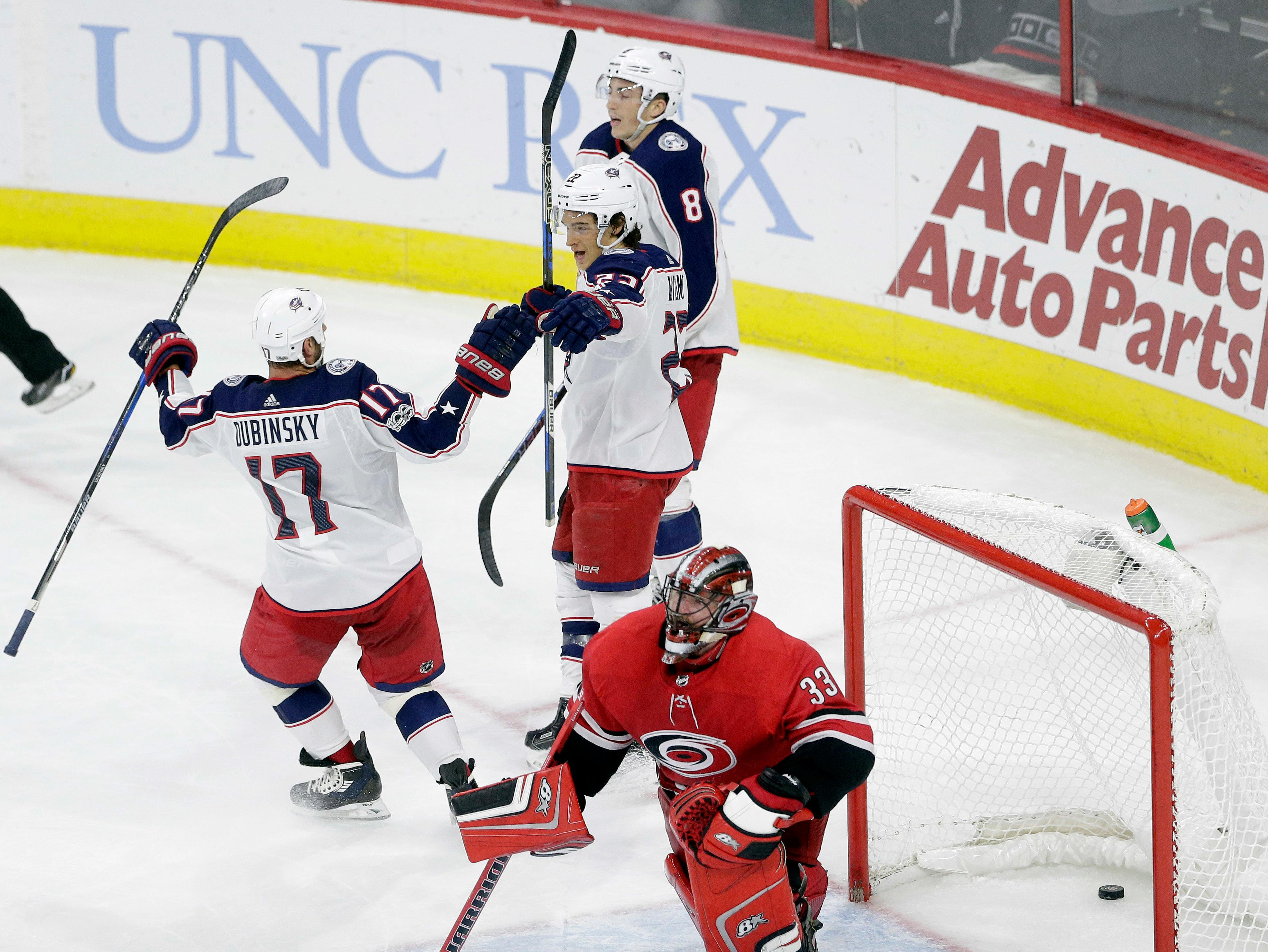 Columbus Blue Jackets' Sonny Milano (22) celebrates his game-winning goal with Brandon Dubinsky (17) and Zach Werenski (8) as Carolina Hurricanes goalie Scott Darling (33) reacts during overtime in an NHL hockey game in Raleigh, N.C., Tuesday, Oct. 10, 2017. Columbus won 2-1 in overtime. (AP Photo/Gerry Broome)
