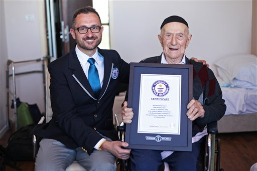 In this photo supplied by the Guinness World Records, Marco Frigatti, Head of Records for Guinness World Records, left, presents Israel Kristal a certificate for being the oldest living man, in Haifa, Israel, Friday, March 11, 2016. (Dvir Rosen/Guinness World Records via AP)