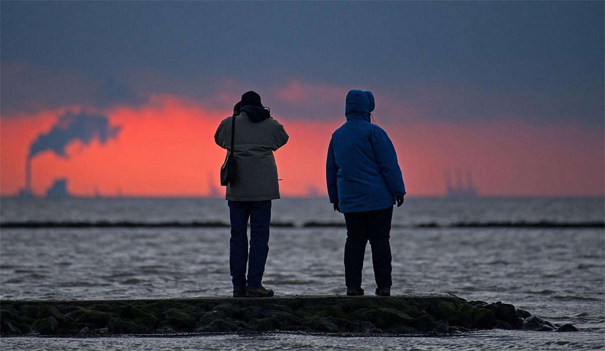 In this Nov. 19, 2016 picture persons watch sunset at the North Sea coast near Dorum-Neufeld, Germany. (Ingo Wagner/dpa via AP)