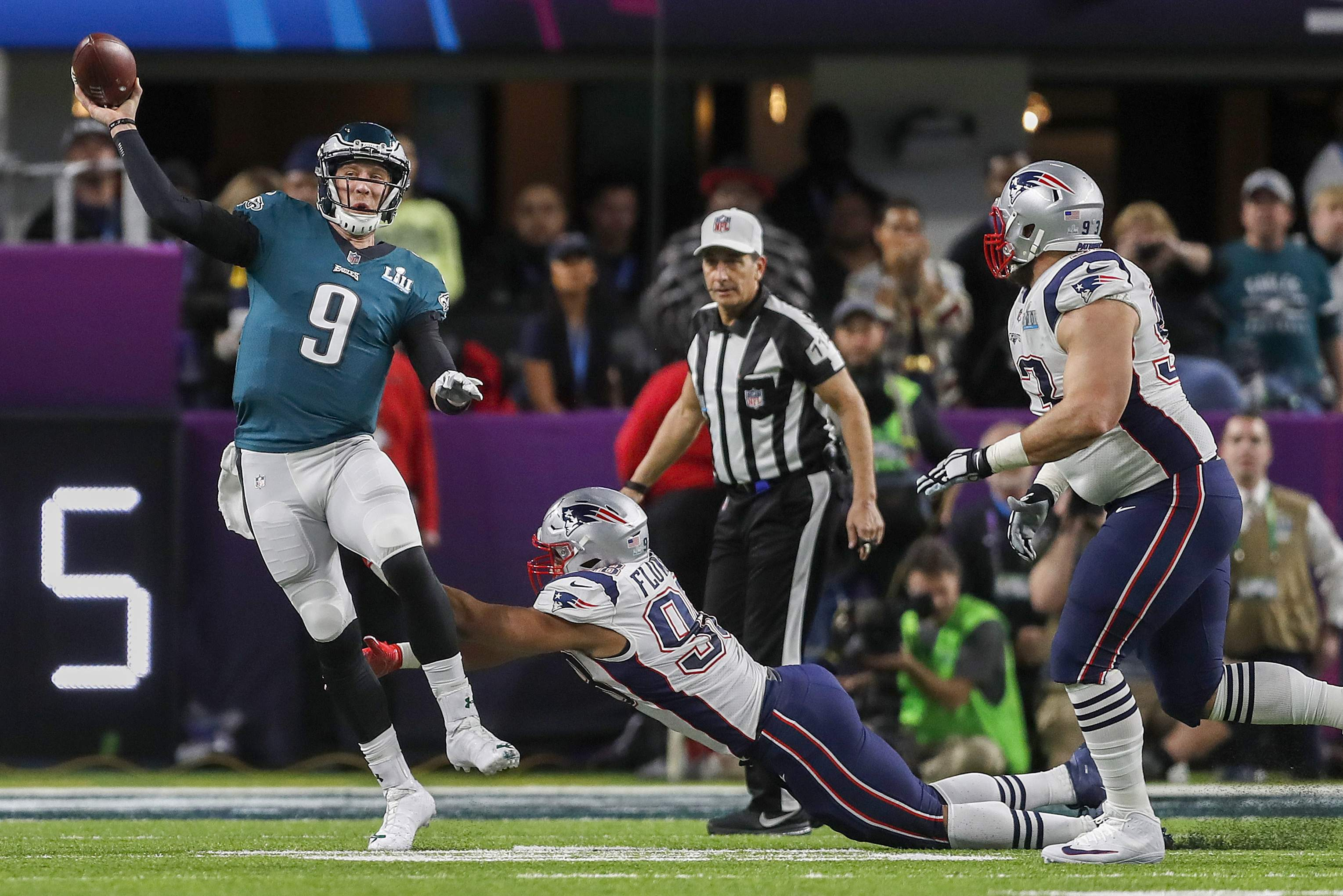 Philadelphia Eagles' Nick Foles (9) is pressured by New England Patriots' Trey Flowers during the first half of the NFL Super Bowl 52 football game Sunday, Feb. 4, 2018, in Minneapolis. (AP Photo/Jeff Roberson)