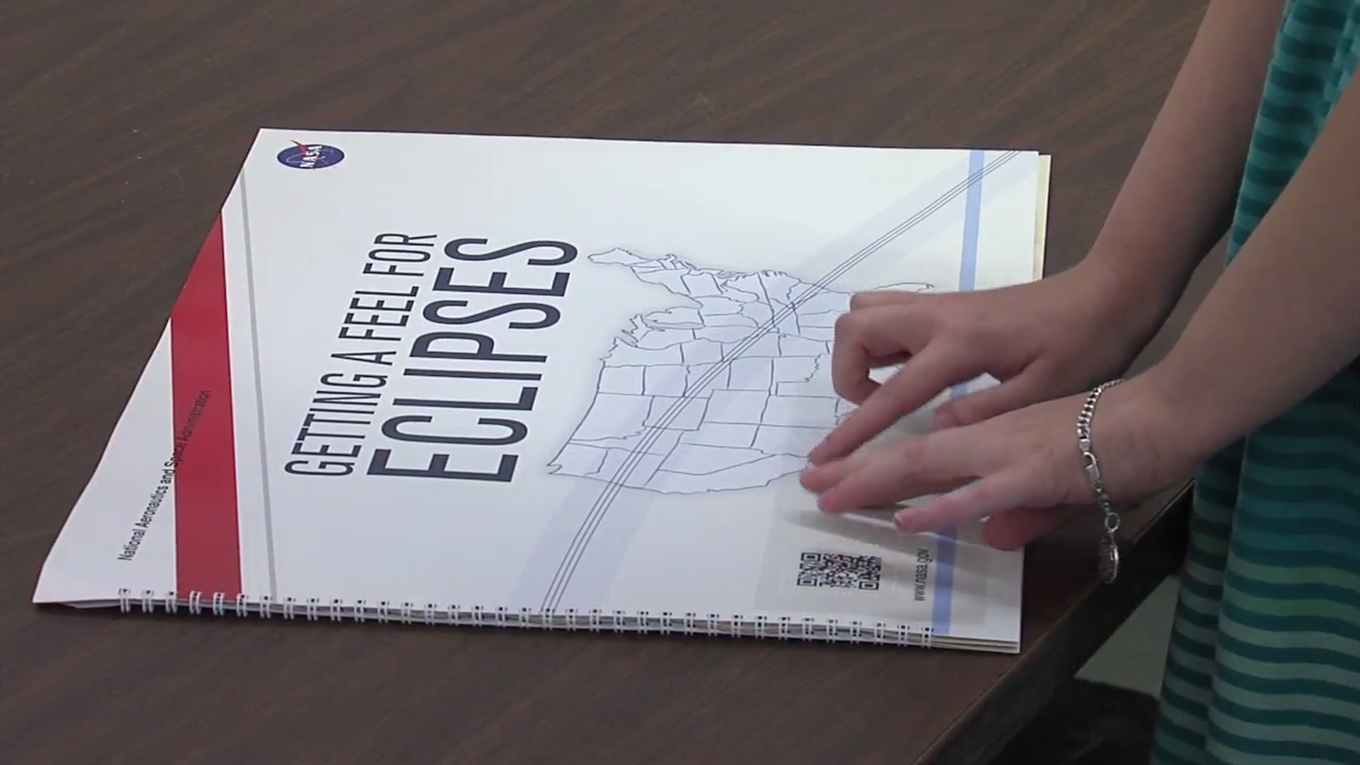 Mariah Williams is blind, but the eclipse has been brought to life for her by a NASA-sponsored tactile graphic book co-authored by one of her professors. (WCIV)