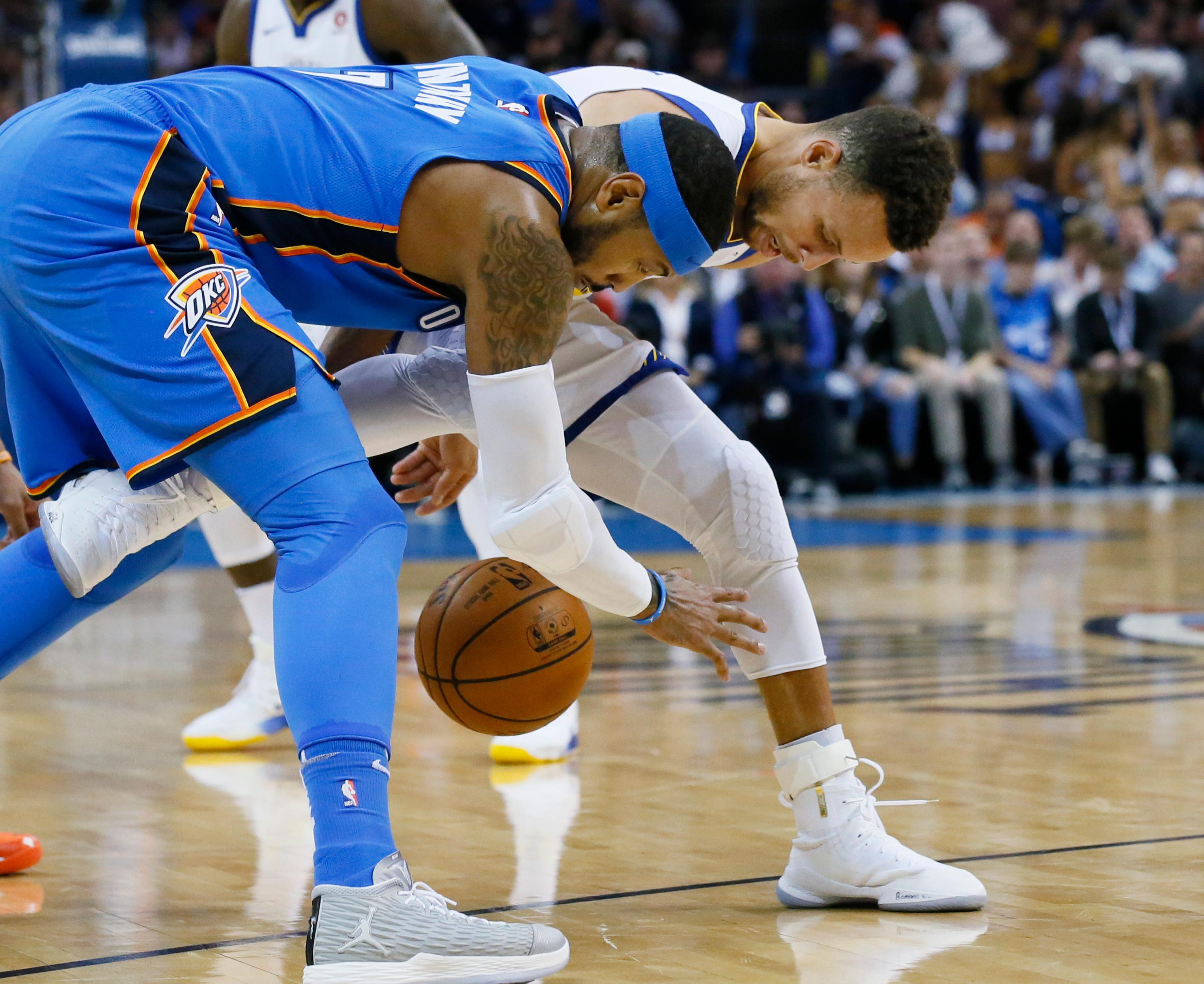 Oklahoma City Thunder forward Carmelo Anthony, left, steals the ball from Golden State Warriors guard Stephen Curry during the first quarter of an NBA basketball game in Oklahoma City, Wednesday, Nov. 22, 2017. (AP Photo/Sue Ogrocki)