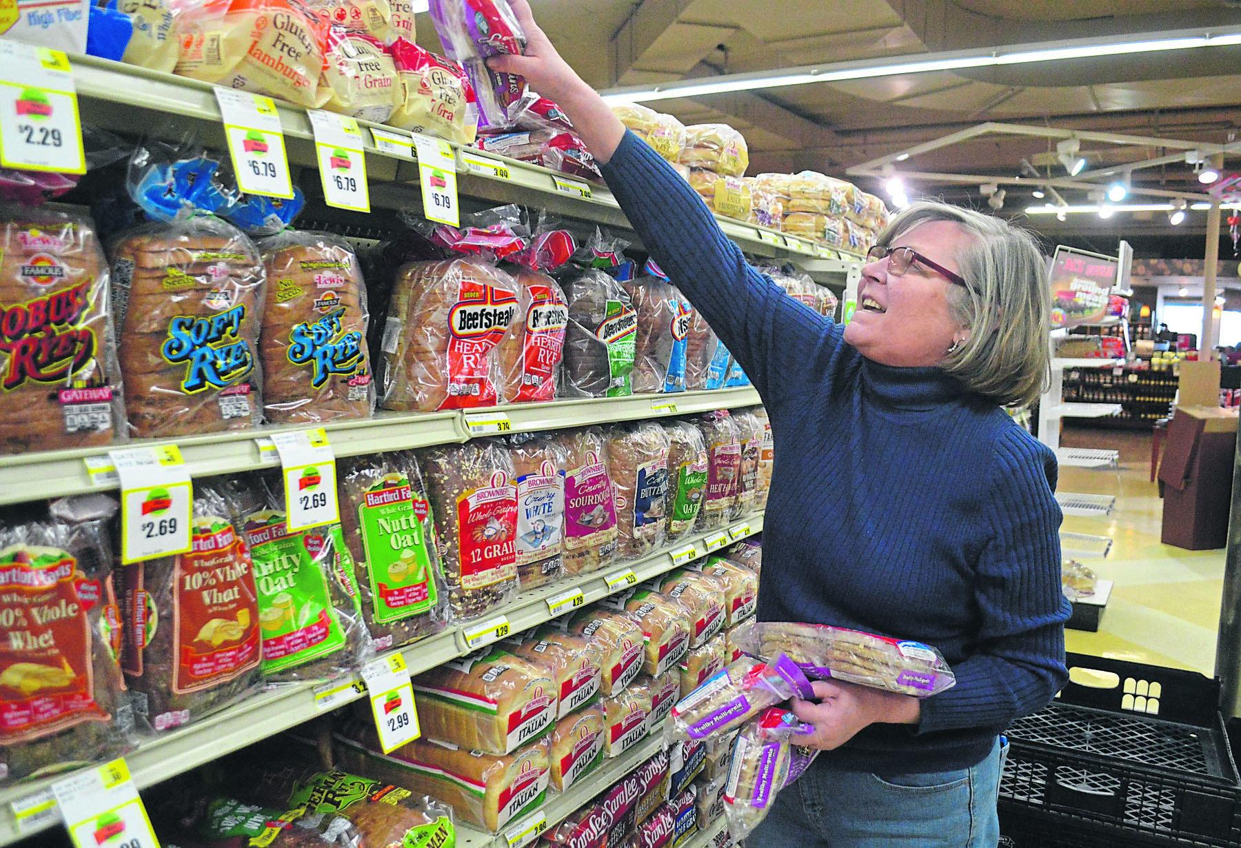Helen Sweeney, an independent distributor for Brownberry Premium Breads, stocks the shelves at Al's Supermarket ahead of another snowstorm, Thursday, Feb. 8, 2018, in La Porte, Ind.  (Jon Gard/The News-Dispatch via AP)