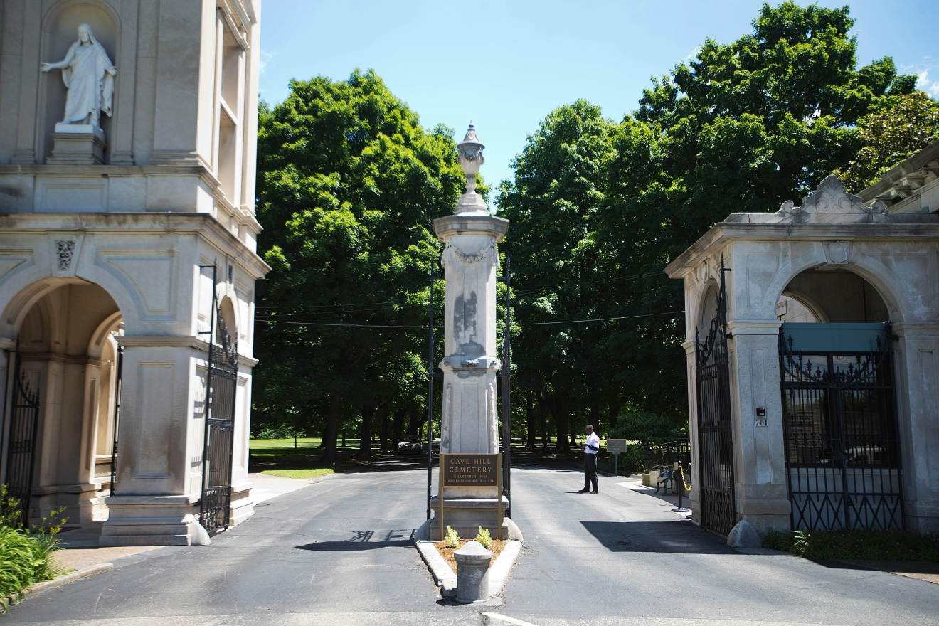 nThe entrance to Cave Hill Cemetery is seen Tuesday, June 7, 2016, in Louisville, Ky. Muhammad Ali's burial will be in Cave Hill Cemetery, the final resting place for many of the city's most prominent residents. The luminaries include Colonel Harlan Sanders, the founder of Kentucky Fried Chicken, whose granite memorial features a bust of the goateed entrepreneur. Ali's gravesite will far more subdued, in contrast to his oversized personality and life. A modest marker, in accord with Muslim tradition, is planned, said his attorney, Ron Tweel. (AP Photo/David Goldman)