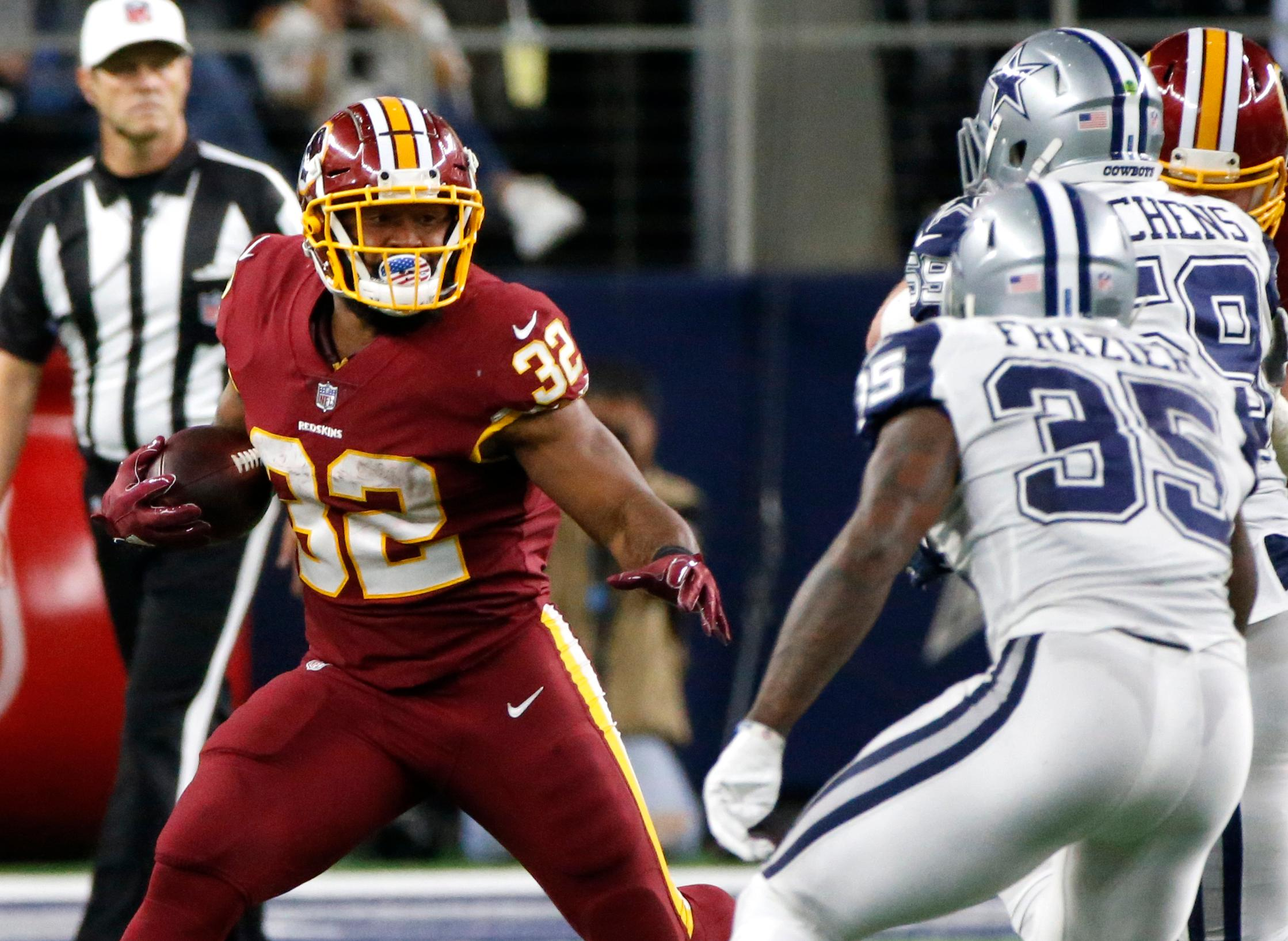 Washington Redskins running back Samaje Perine (32) carries the ball as Dallas Cowboys safety Kavon Frazier (35) and Anthony Hitchens, right rear, defend in the second half of an NFL football game, Thursday, Nov. 30, 2017, in Arlington, Texas. (AP Photo/Michael Ainsworth)