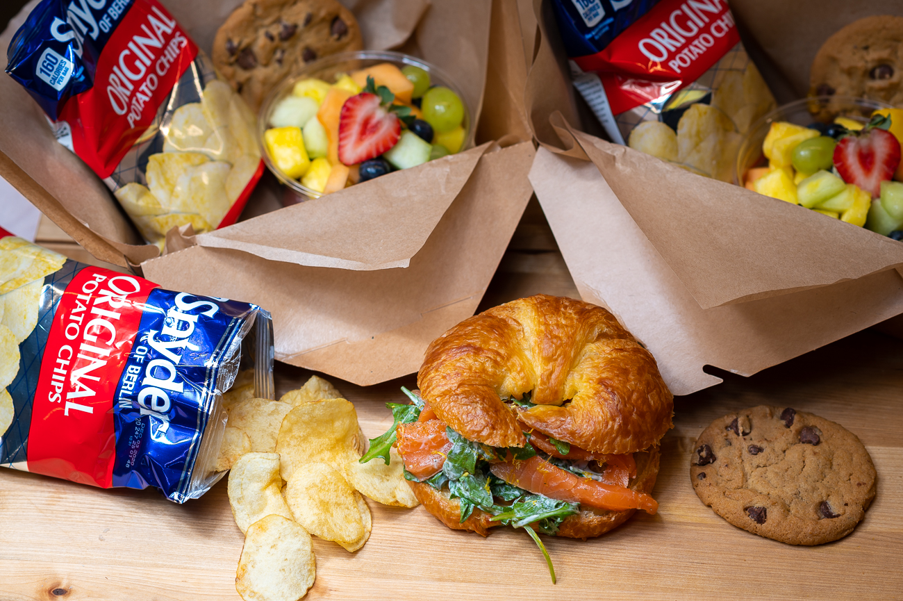 Their boxed lunches are available through the end of the year. Pictured: Atlantic smoked salmon with arugula, lemon, capers, and chives on a fresh croissant. Each boxed lunch comes with a bagged snack, cookie, and fruit salad. / Image: Phil Armstrong, Cincinnati Refined // Published: 11.6.20