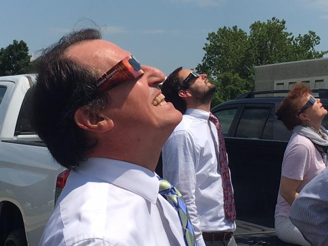 District Attorney Greg Newman watches the August 21, 2017, eclipse from the Henderson County Courthouse parking lot. (Photo credit: WLOS Staff)