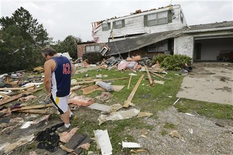 Travis Randall walks through the debris-strewn yard of his parent's home in Hickman, Neb., Friday after it was struck by a tornado.
