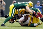 Washington quarterback Robert Griffin III loses his helmet as he is sacked by Green Bay Packers' Clay Matthews and A.J. Hawk Sept. 15, 2013, in Green Bay.
