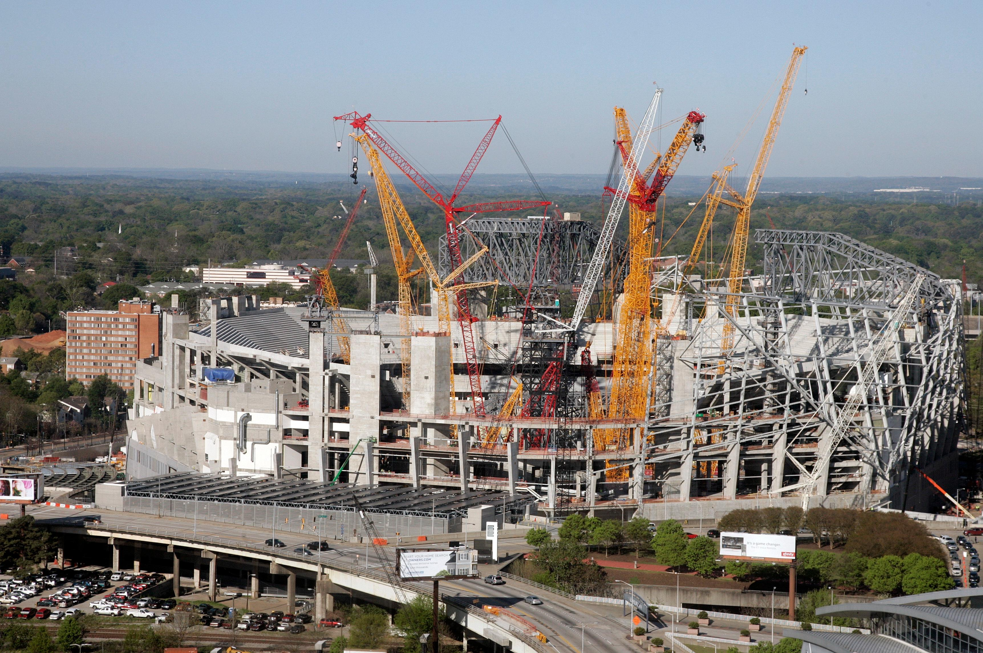 "In this April 5, 2016 photo, construction crews work on the the Mercedes-Benz stadium, in Atlanta. The new $1.5 million stadium is home to the National Football League's Atlanta Falcons and Major League Soccer's Atlanta United. It features a retractable roof; a 1,100-foot ""halo board"" video display; and a giant steel sculpture of a Falcon with its 70-foot wingspan at one of the main entrances. (AP Photo/John Bazemore)"