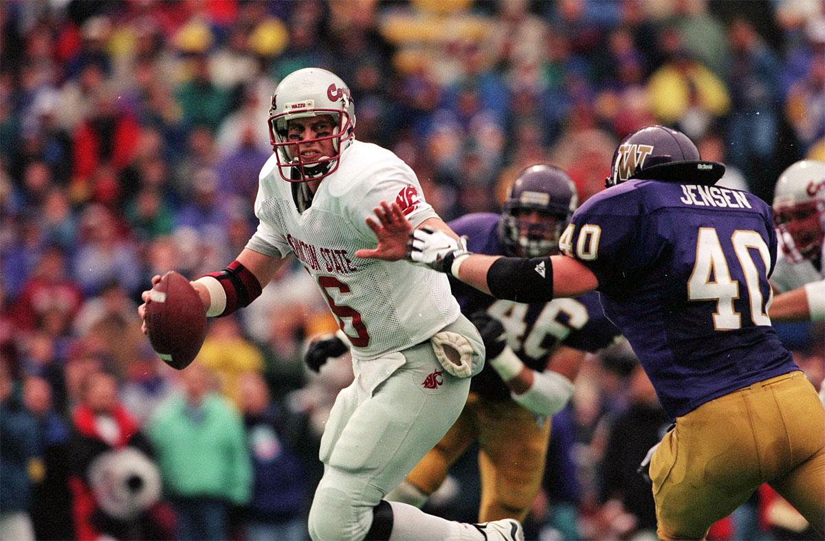 FILE - In this Nov. 22, 1997, file photo, Washington State quarterback Ryan Leaf is pressured by Washington in the NCAA college football Apple Cup game, in Seattle. Twenty years ago, the senior-laden upstart team from Washington State erased 67 years of hardship with one magical season that ended with the school's first Rose Bowl berth since before World War II. The clincher came on a dreary November day in Seattle that concluded with those in crimson and gray storming the turf of Husky Stadium and celebrating an Apple Cup victory over the Huskies. (Rod Mar/The Seattle Times via AP, File)