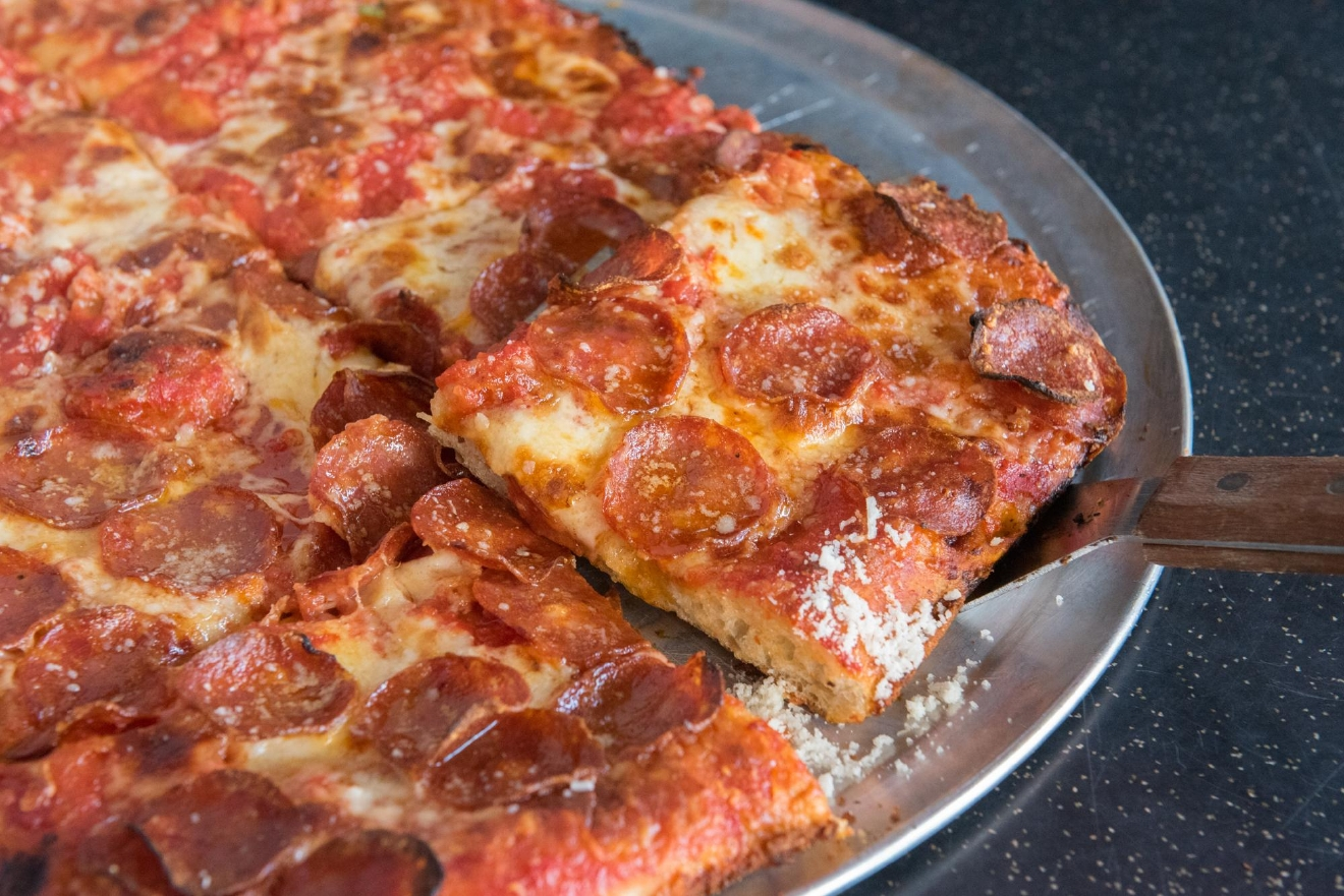 "Dino's Tomato Pie is Capitol Hill's dive-bar pizzeria serving New Jersey–style traditional round pies and square Sicilian options. Lovingly called ""The Second Best Pizza in Seattle,"" the spot is only second to it's older sibling, Delancey.{ }(Image courtesy of Dino's Tomato Pie)"