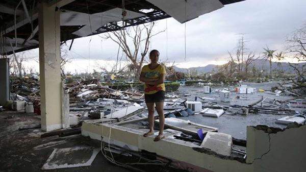 A woman stands amidst the devastation brought about by powerful Typhoon Haiyan at Tacloban city, in Leyte province, central Philippines