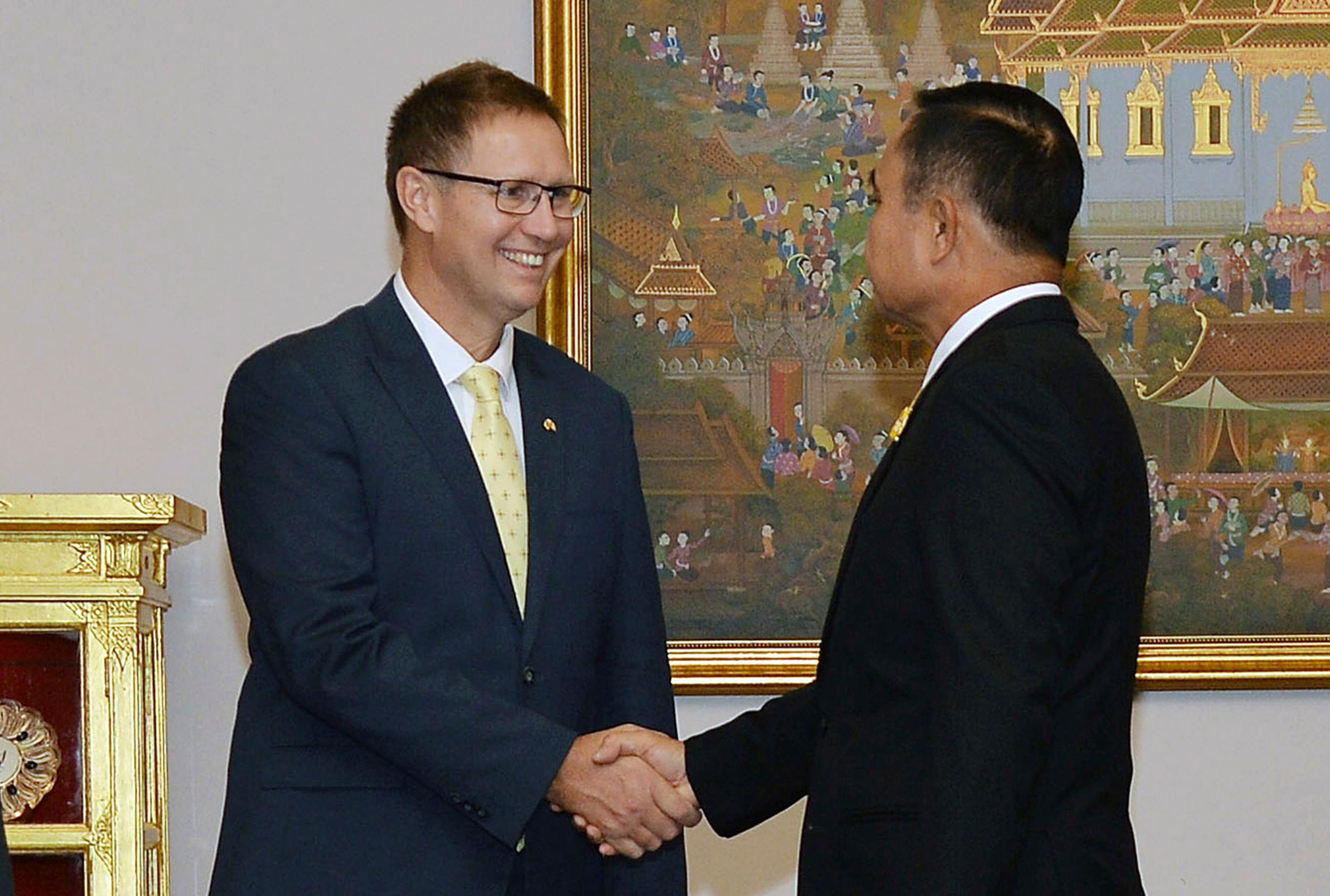 In this photo released by Government Spokesman Office, Richard Harris, left, an Australian member of the Thai cave rescue team, shakes hands with Thailand's Prime Minister Prayuth Chan-ocha after receiving the Member of the Most Admirable Order of the Direkgunabhorn during the royal decoration ceremony at the Royal Thai Government House in Bangkok, Thailand, Friday, April 19, 2019. (Government Spokesman Office via AP)
