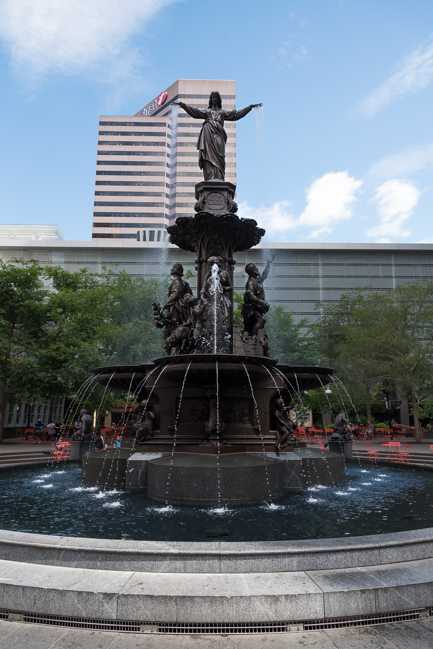 The Tyler-Davidson Fountain on Fountain Square is covered in many bronze statues and bas reliefs representing the benefits, pleasures, and necessities of water. The fountain, designed by Ferdinand von Miller and August von Kreling in Munich, Germany years before it came to Cincinnati, was commissioned by local businessman Henry Probasco for his deceased brother-in-law, Tyler Davidson. Probasco thought the theme of water ideal for Cincinnati's status as a river town, and the fountain was unveiled on 5th Street in 1871. It's been the symbol of Cincinnati for nearly 150 years. / Image: Phil Armstrong, Cincinnati Refined // Published: 5.31.18