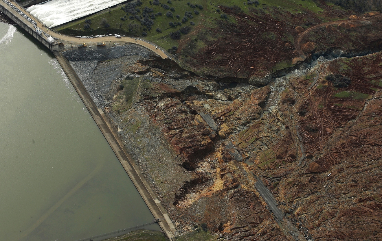 This photo shows erosion caused when overflow water cascaded down the emergency spillway of Oroville Dam, Monday, Feb. 13, 2017, in Oroville, Calif. Water levels dropped Monday at the nation's tallest dam, easing slightly the fears of a catastrophic spillway collapse that prompted authorities to order people to leave their homes downstream. At upper left, water flows down the dams main spillway. (AP Photo/Rich Pedroncelli)