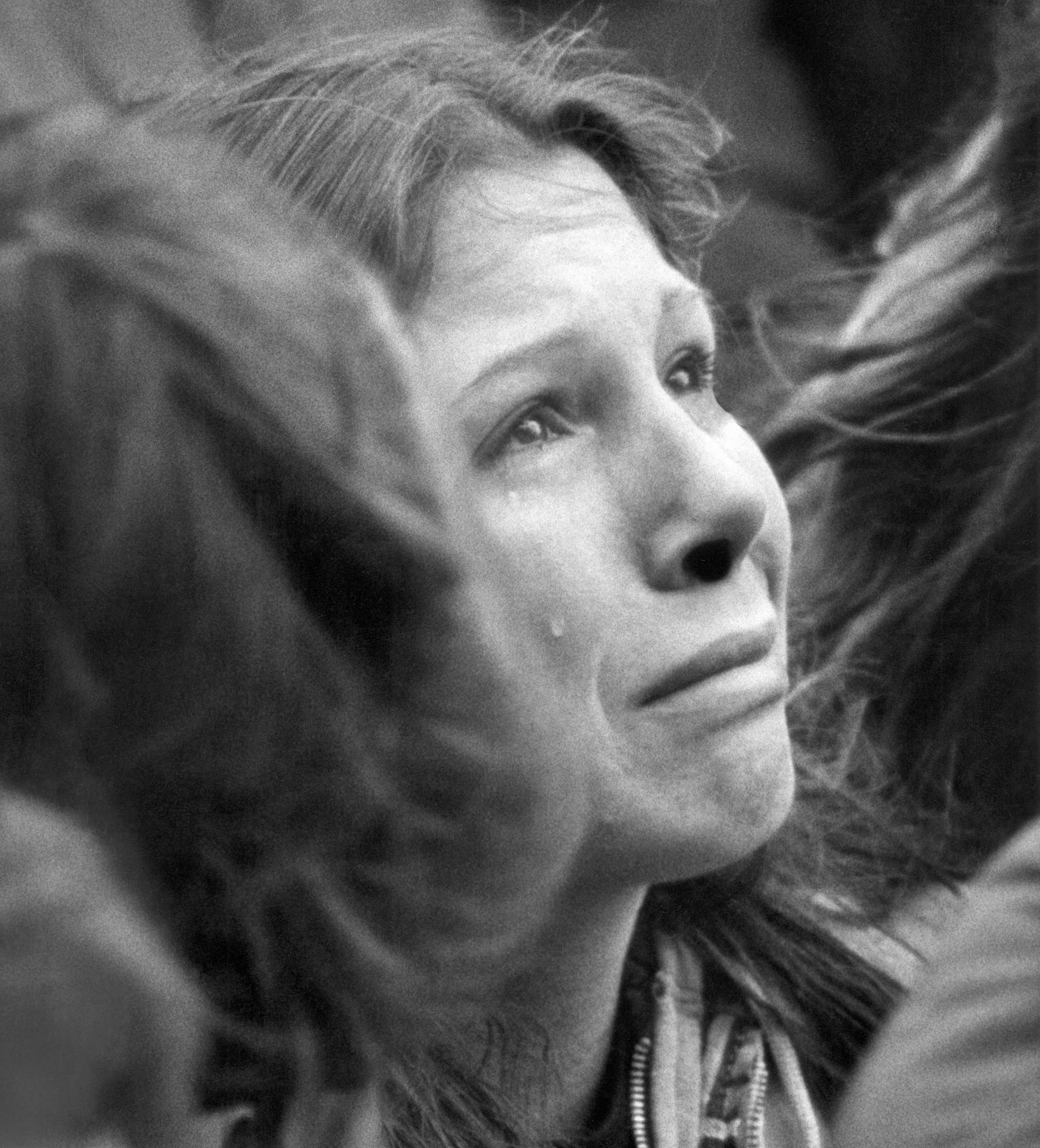FILE - In this Dec. 14, 1980, file photo, a woman weeps during a ten minute silent vigil for John Lennon held in front of Trinity Church in Boston. An estimated crowd of 2,000 people came to honor the former Beatle who was murdered in New York. Thirty-five years ago on Dec. 8, Mark David Chapman shot and killed Lennon, a former Beatles member. (AP Photo/John Martell, File)