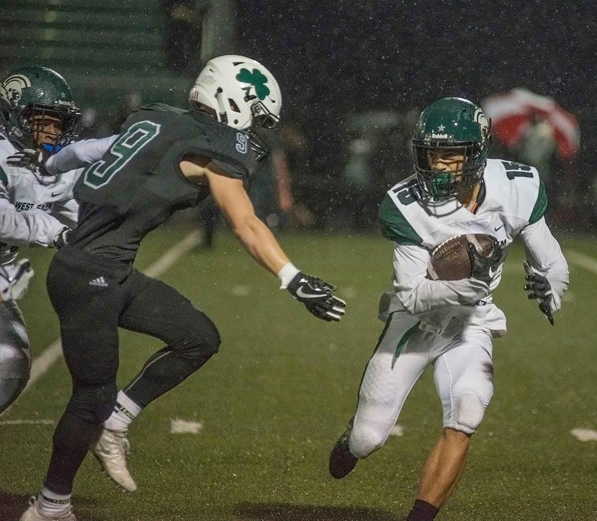 West Salem Titans wide receiver Anthony Gould (#15) dodges Sheldon Irish wide receiver Jack Folsom (#9).  On a rainy Monday evening, Sheldon defeated West Salem 41 to 7 at their home field. The game had been postponed from Friday due to unhealthy levels of smoke in the atmosphere from nearby forest fires. Abigail Winn, Oregon News Lab