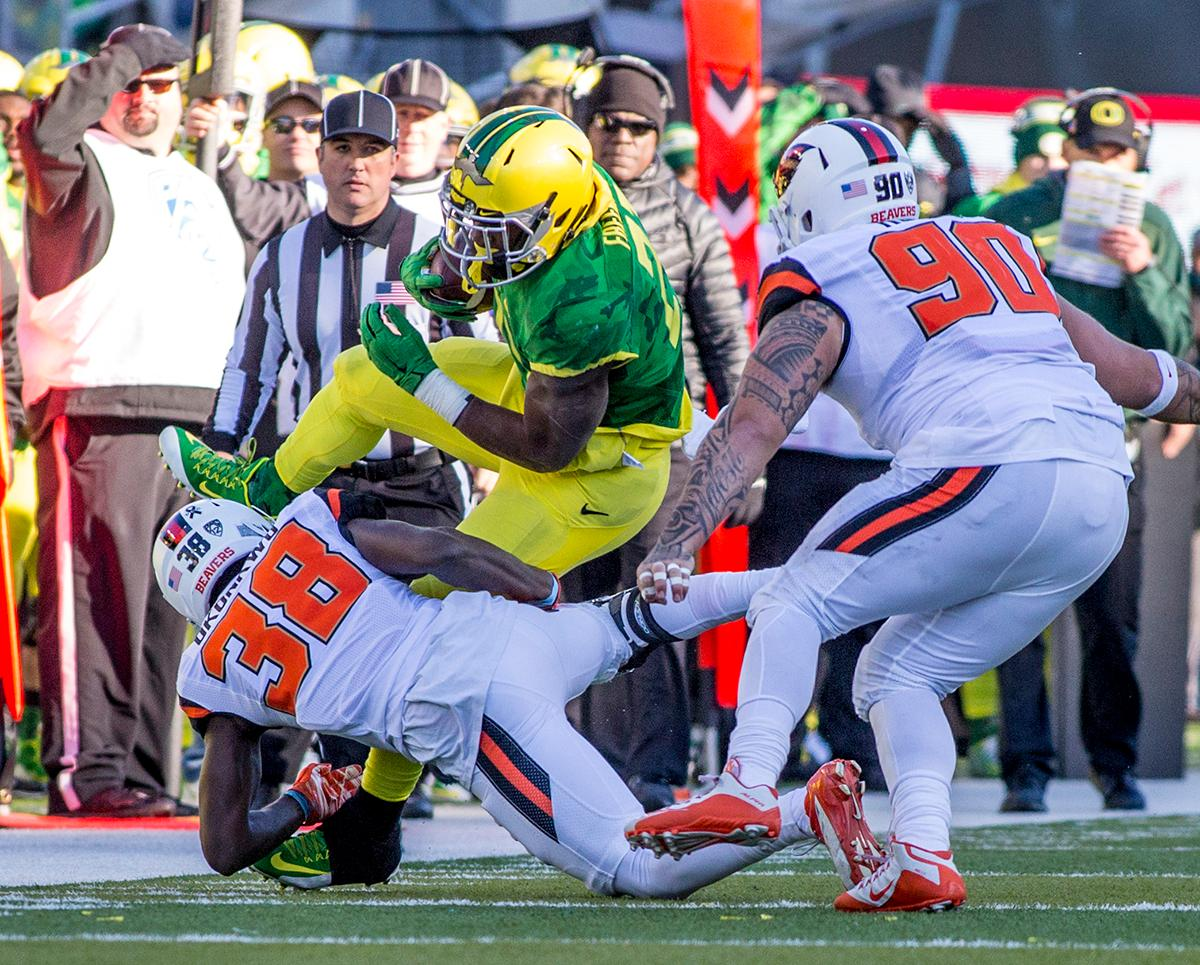 Oregon Ducks Royce Freeman (#21) attempts to power his way through Oregon State Beavers Charles Okonkwo (#38) Ali'i Robins (#90) n the Civil War game in Autzen Stadium. At the half the Ducks led the Beavers 31 - 7. Photo by Katie Pietzold, Oregon News Lab