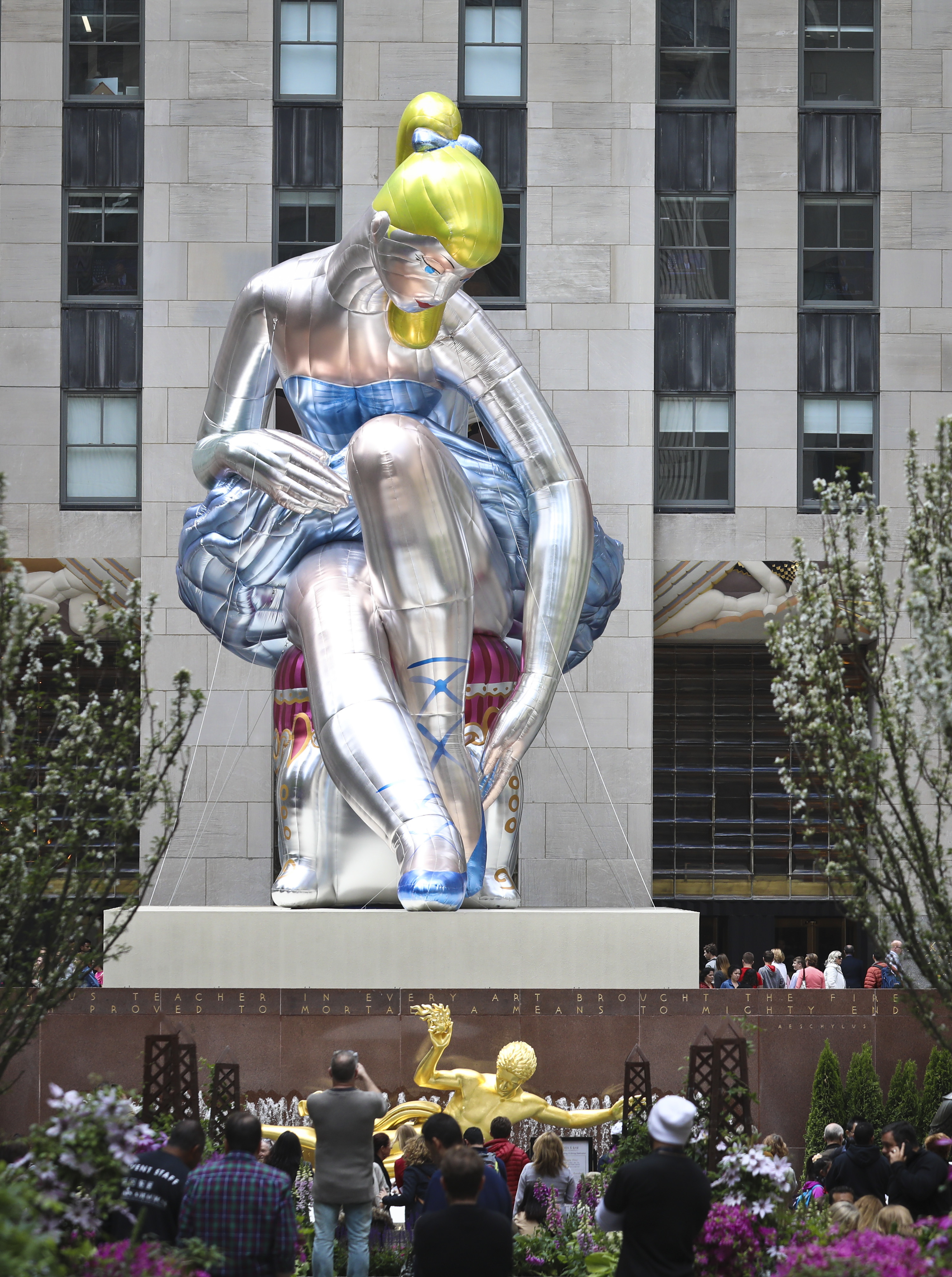 """Seated Ballerina"", center, the public art exhibition of a 45-foot tall inflatable nylon sculpture depicting a seated ballerina from artist Jeff Koons' Antiquity series, is displayed at Rockefeller Center after it was unveiled Friday May 12, 2017, in New York. (AP Photo/Bebeto Matthews)"