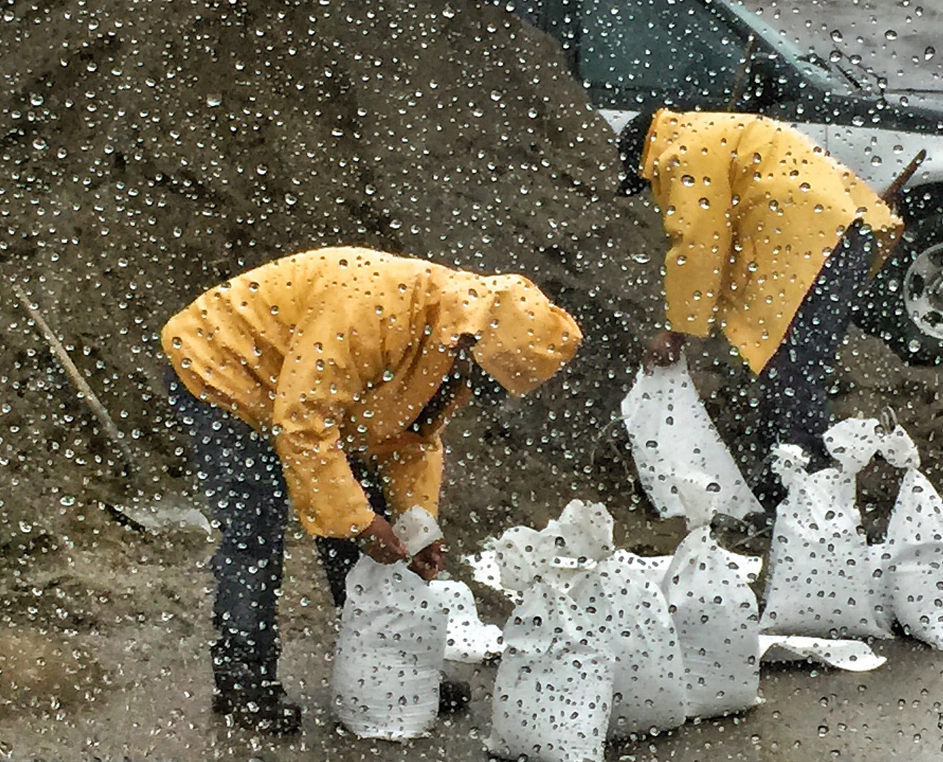 In this photo taken through a glass window, released by Santa Barbara County Fire Department, people fill up sandbags under the rain in Santa Barbara, Calif., Monday, Jan. 8, 2018. Storms brought rain to California on Monday and increased the risk of mudslides in fire-ravaged communities. (Mike Eliason/Santa Barbara County Fire Department via AP)