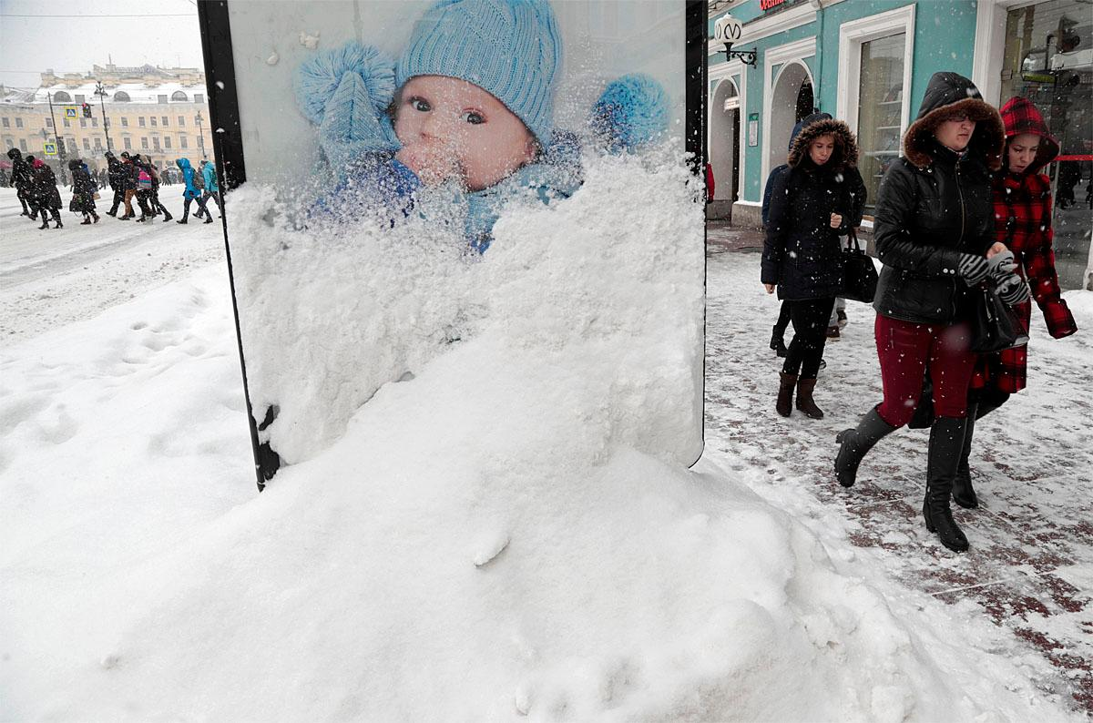 People walk in the snow in St. Petersburg, Russia, Tuesday, Nov. 8, 2016. Low temperatures caused two days of snowfall in St. Petersburg. (AP Photo/Dmitri Lovetsky)