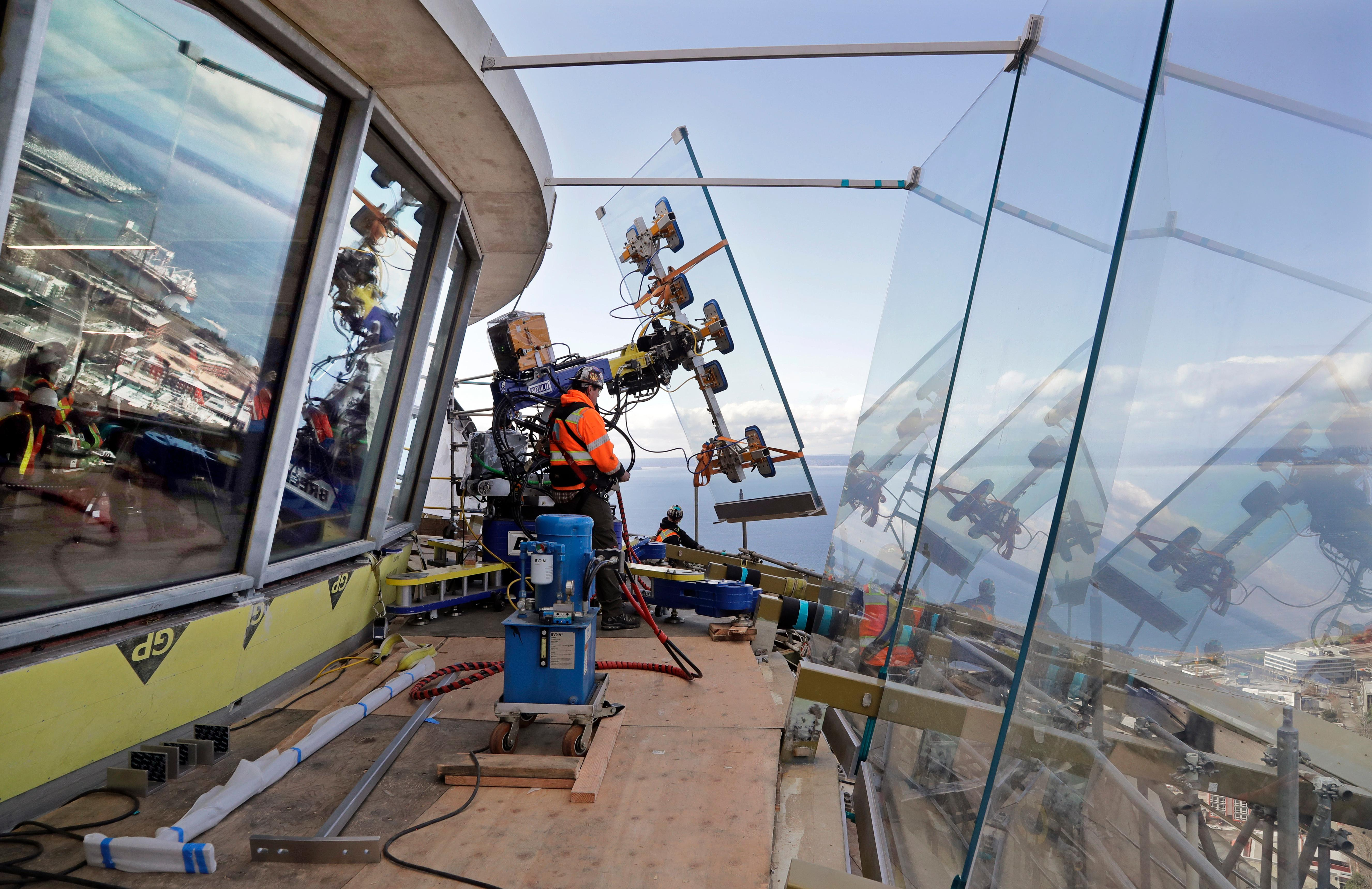 FILE - In this March 20, 2018, file photo, a one-ton glass panel is moved into position on the Space Needle's observation deck in Seattle.  The 56 year-old Space Needle is set to unveil a $100 million renovation next month against the backdrop of a booming tourism industry. Seattle's Wright family, which built and owns the Space Needle, is installing floor-to-ceiling glass in the observation deck and remodeling the restaurant in the first phase of the renovation.  (AP Photo/Elaine Thompson)