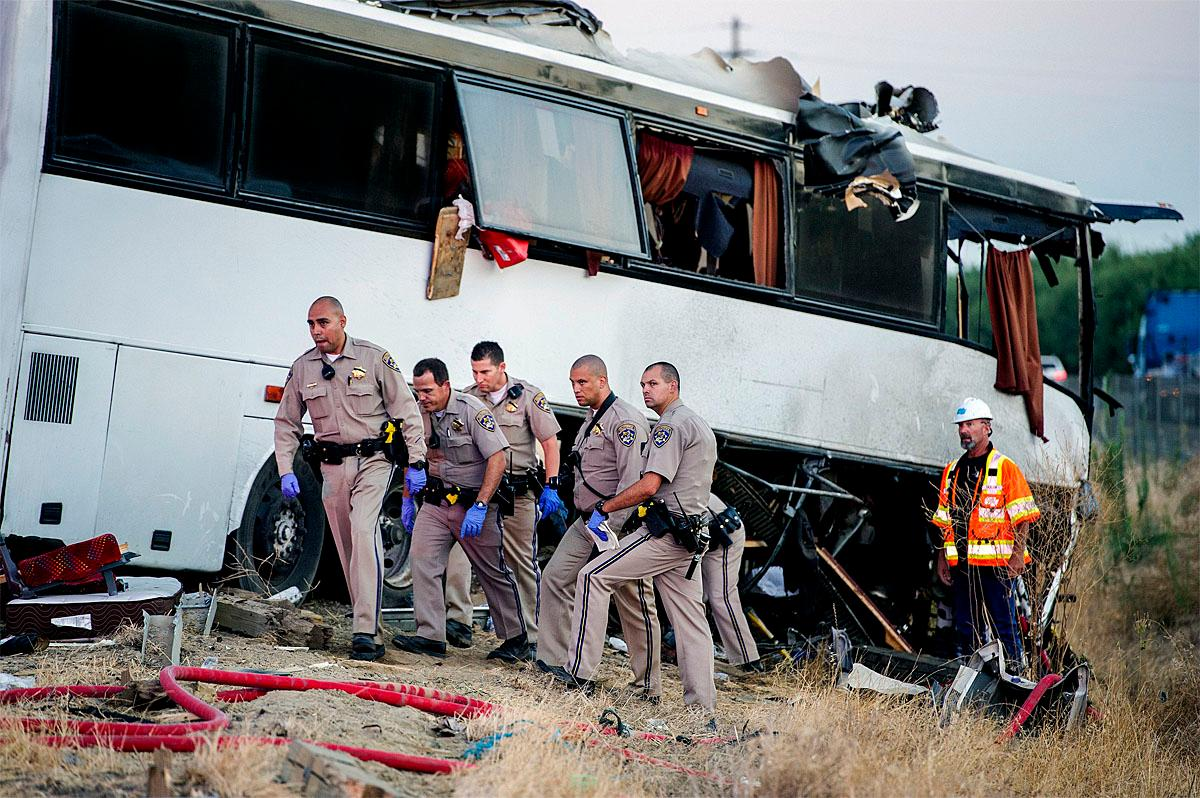 California Highway Patrol officers investigate the scene of a charter bus crash on northbound Highway 99 between Atwater and Livingston, Calif., Tuesday, Aug. 2, 2016. The bus veered off the central California freeway before dawn Tuesday and struck a pole that sliced the vehicle nearly in half, authorities said. (Andrew Kuhn/Merced Sun-Star via AP)